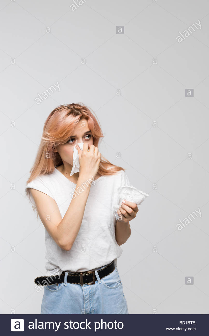 Portrait of cute woman blowing her nose into paper napkin,looks to the source of the allergy/cold, sneezing, allergy symptoms, flu, rhinitis, sickness - Stock Image