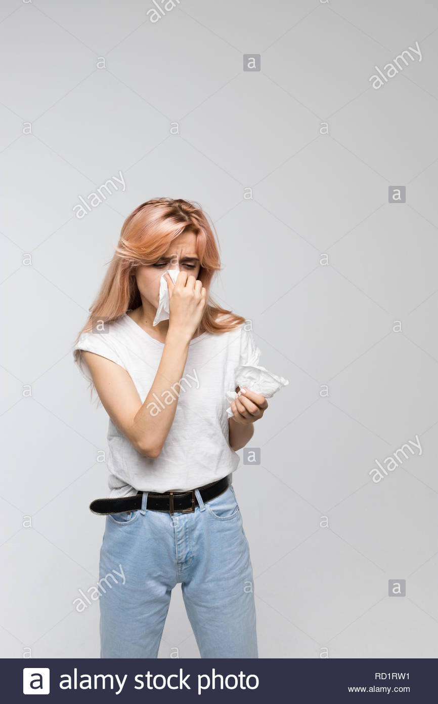 Portrait of cute woman blowing her nose into paper napkin, looks to her hand/cold, sneezing, allergy symptoms, flu, rhinitis, sickness. - Stock Image