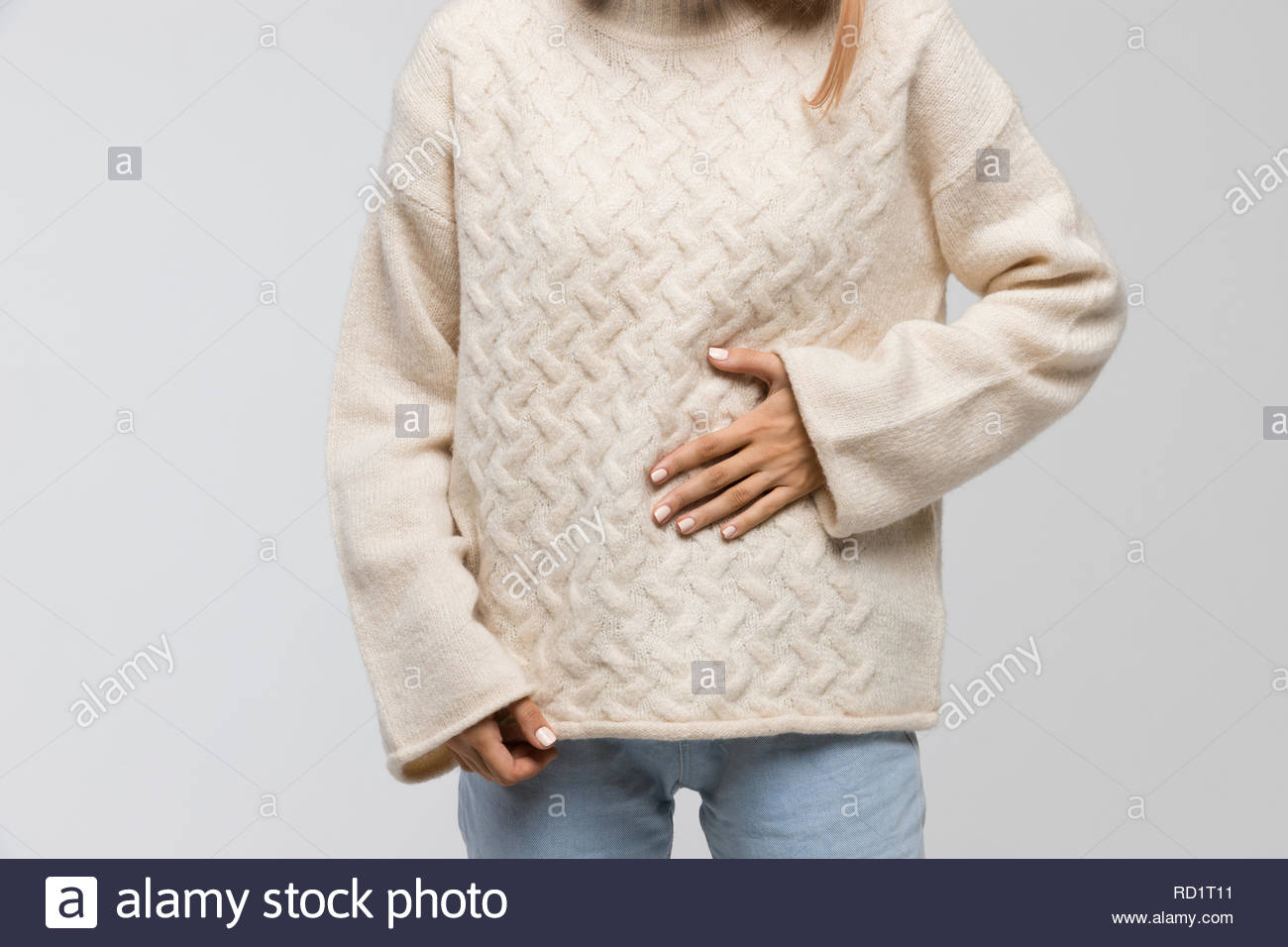 Close-up shot of young woman in white sweater suffering from stomach ache, having menstruation pain, feels bad, front view. Pain in stomach, menstrual. - Stock Image