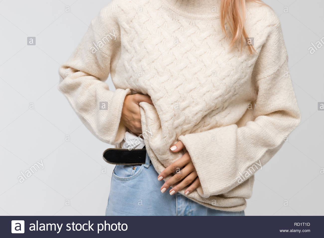 Cropped shot of young woman in white sweater suffering from stomach ache, having menstruation pain, feels bad, front view. Pain in stomach, PMS. - Stock Image