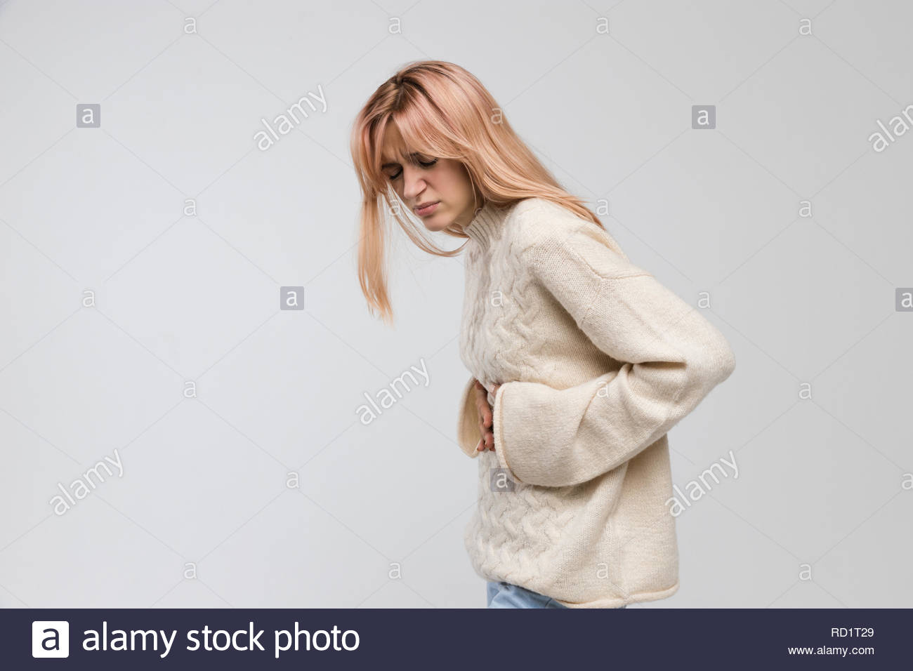 Young cute woman in white sweater suffering from stomach ache, having menstruation pain, feels bad, abdominal cramps, side view. Menstrual period. - Stock Image