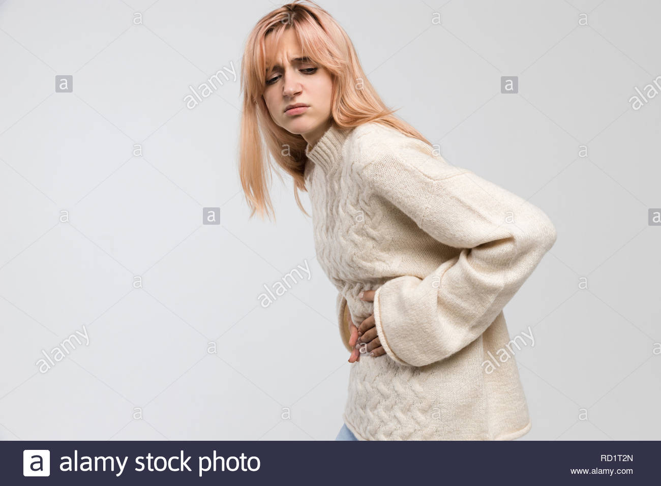 Close up shot of woman in white sweater suffering from stomach ache, having menstruation pain, feels bad, abdominal cramps, side view, PMS. - Stock Image