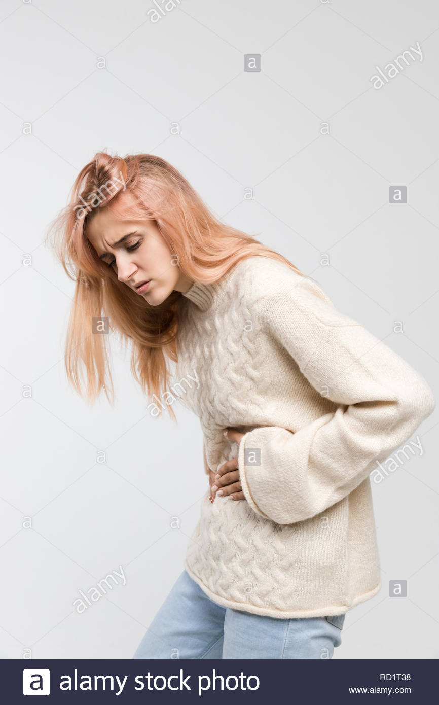 Vertical portrait of woman in white sweater suffering from stomach ache, having menstruation pain, feels bad, abdominal cramps, side view, PMS. - Stock Image