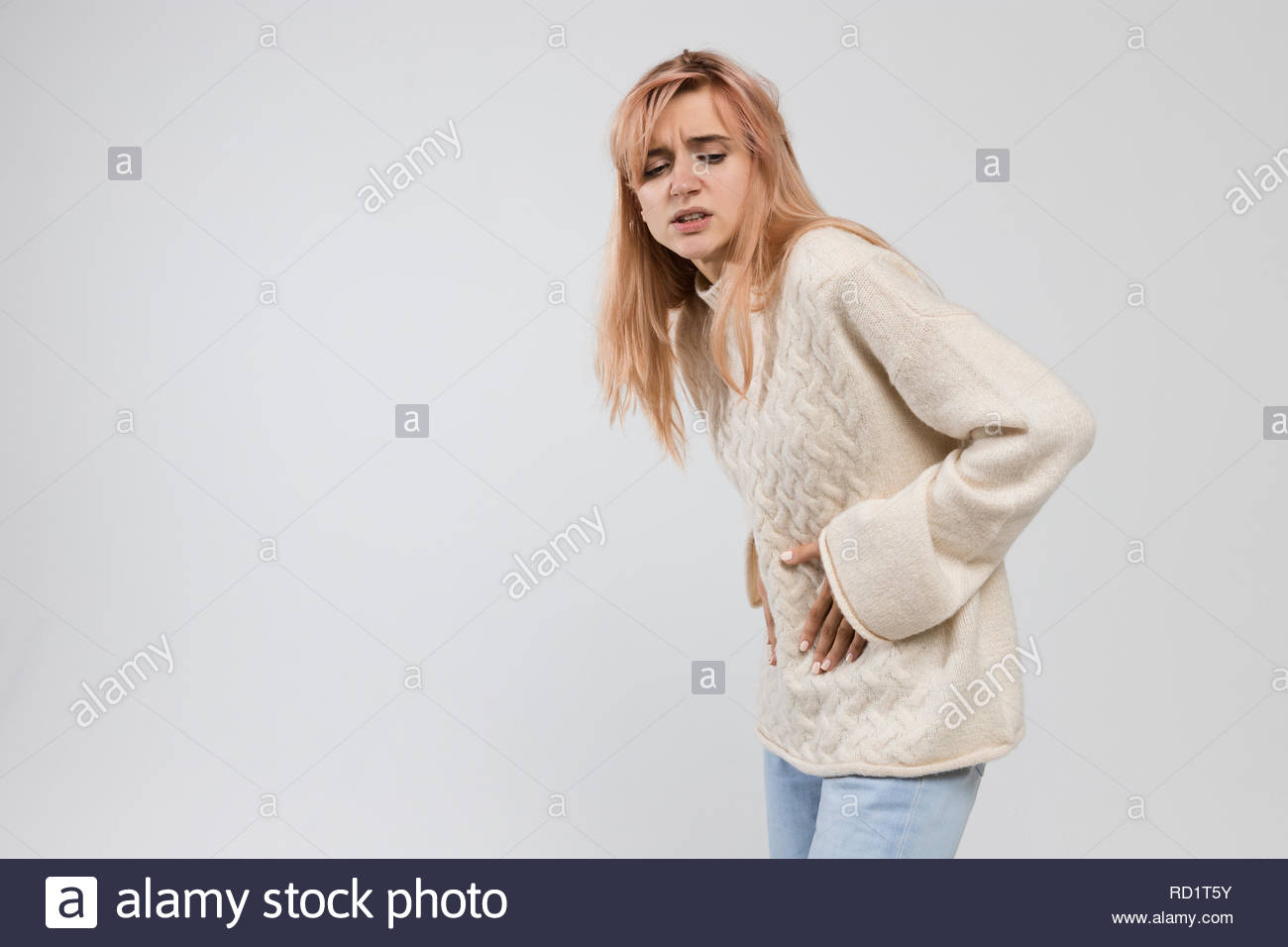 Portrait of woman in white sweater suffering from abdominal pain, having menstruation pain, feels bad, wrinkle in pain, side view, menstrual period. - Stock Image