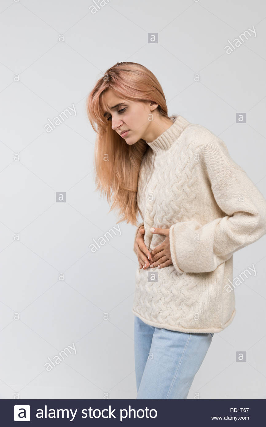Vertical shot of woman in white sweater suffering from stomach ache, having menstruation pain, feels bad, abdominal cramps, side view, PMS. - Stock Image