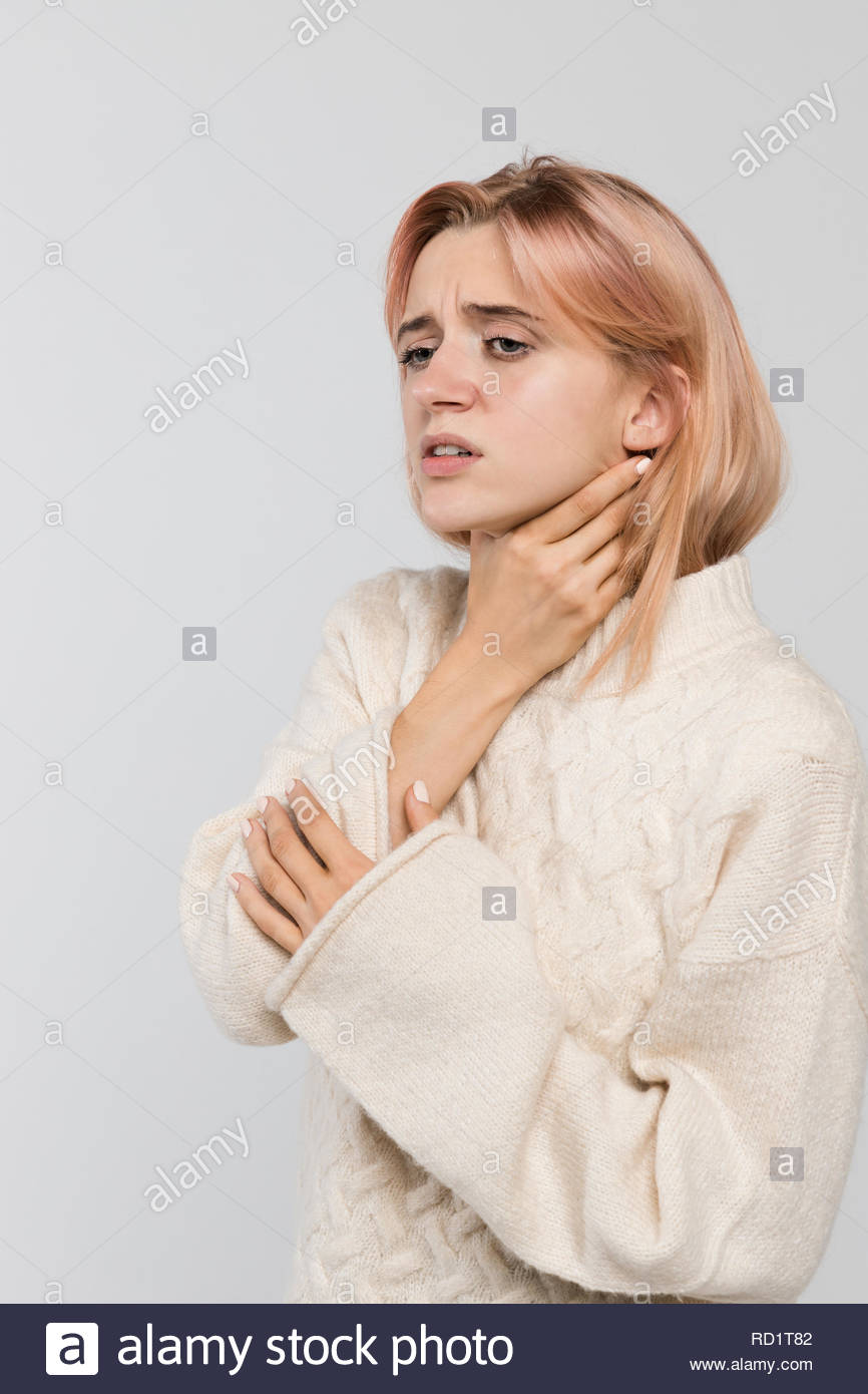 Studio portrait of young unhealthy blonde woman in warm sweater holding her throat, sore throat/suffers from cold and flu, coughing a lot. - Stock Image