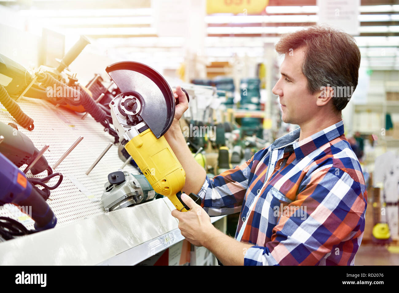 Man shopping for angle grinder in hardware store close-up - Stock Image