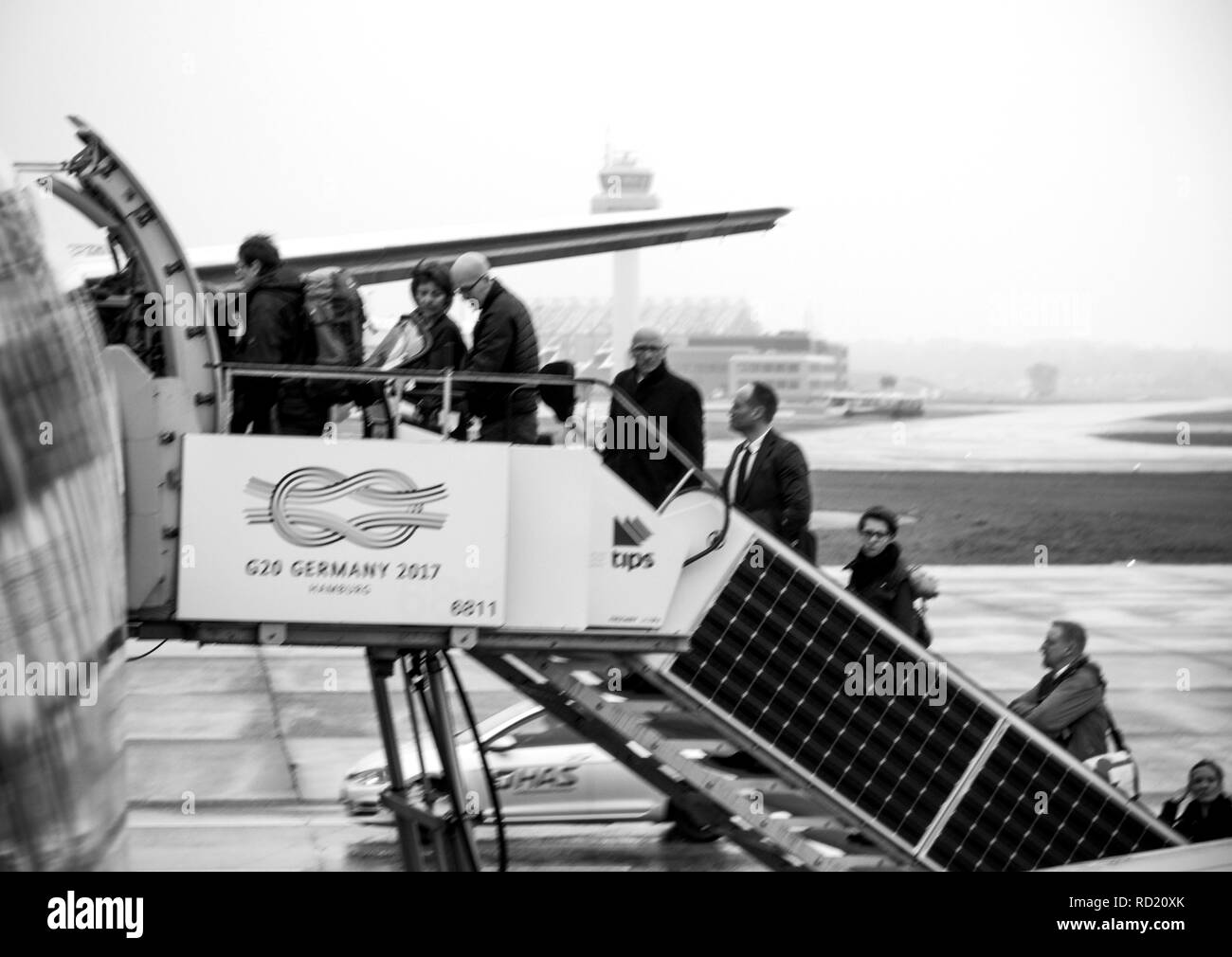 HAMBURG, GERMANY - MAR 22, 2018: Defocused black and white of people entering EasyJet airplane early in the morning in Flughafen Hamburg through rear passenger door jetway stairs - Stock Image