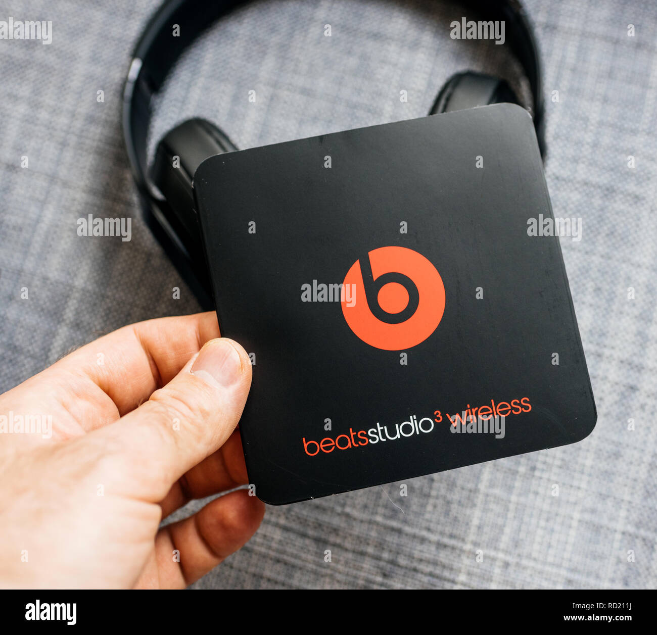 PARIS, FRANCE - MAR 31, 2018: Man unboxing new Apple Beats By Dr Dre Beats Studio 3 Wireless headphones with Pure Adaptive Noise Canceling Pure ANC - holding instruction manual  - Stock Image