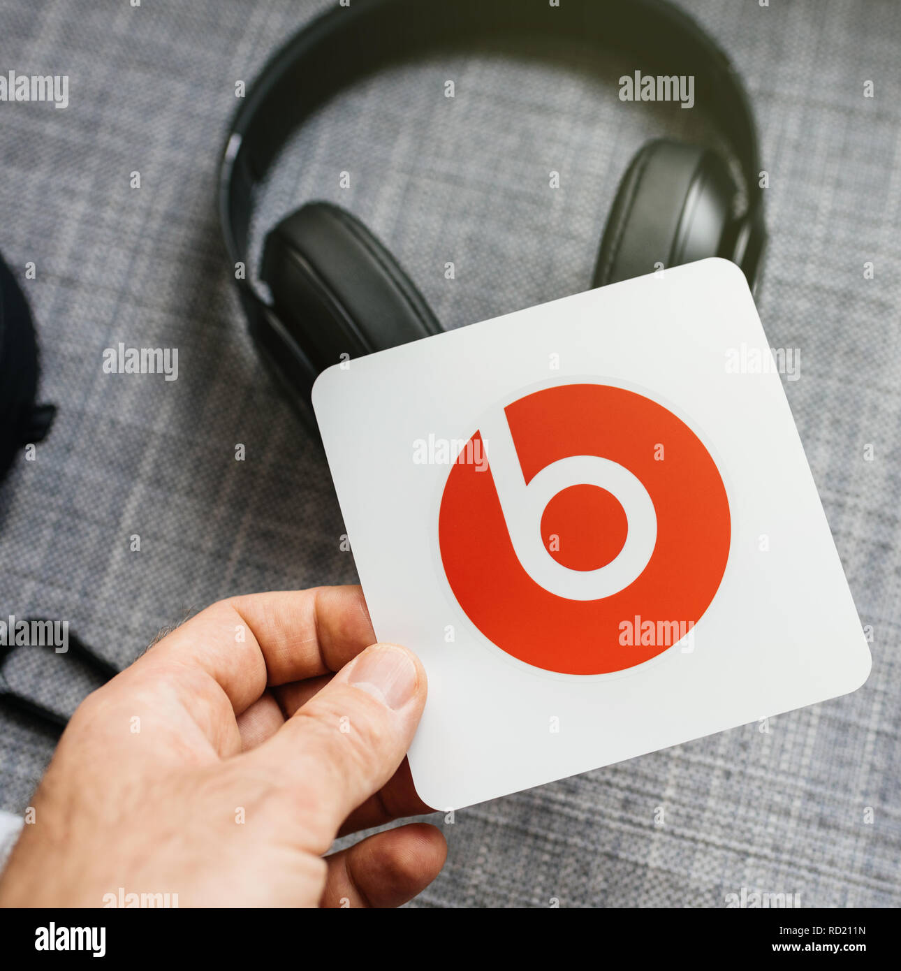 PARIS, FRANCE - MAR 31, 2018: Man unboxing new Apple Beats By Dr Dre Beats Studio 3 Wireless headphones with Pure Adaptive Noise Canceling Pure ANC - holding the supplied sticker - Stock Image