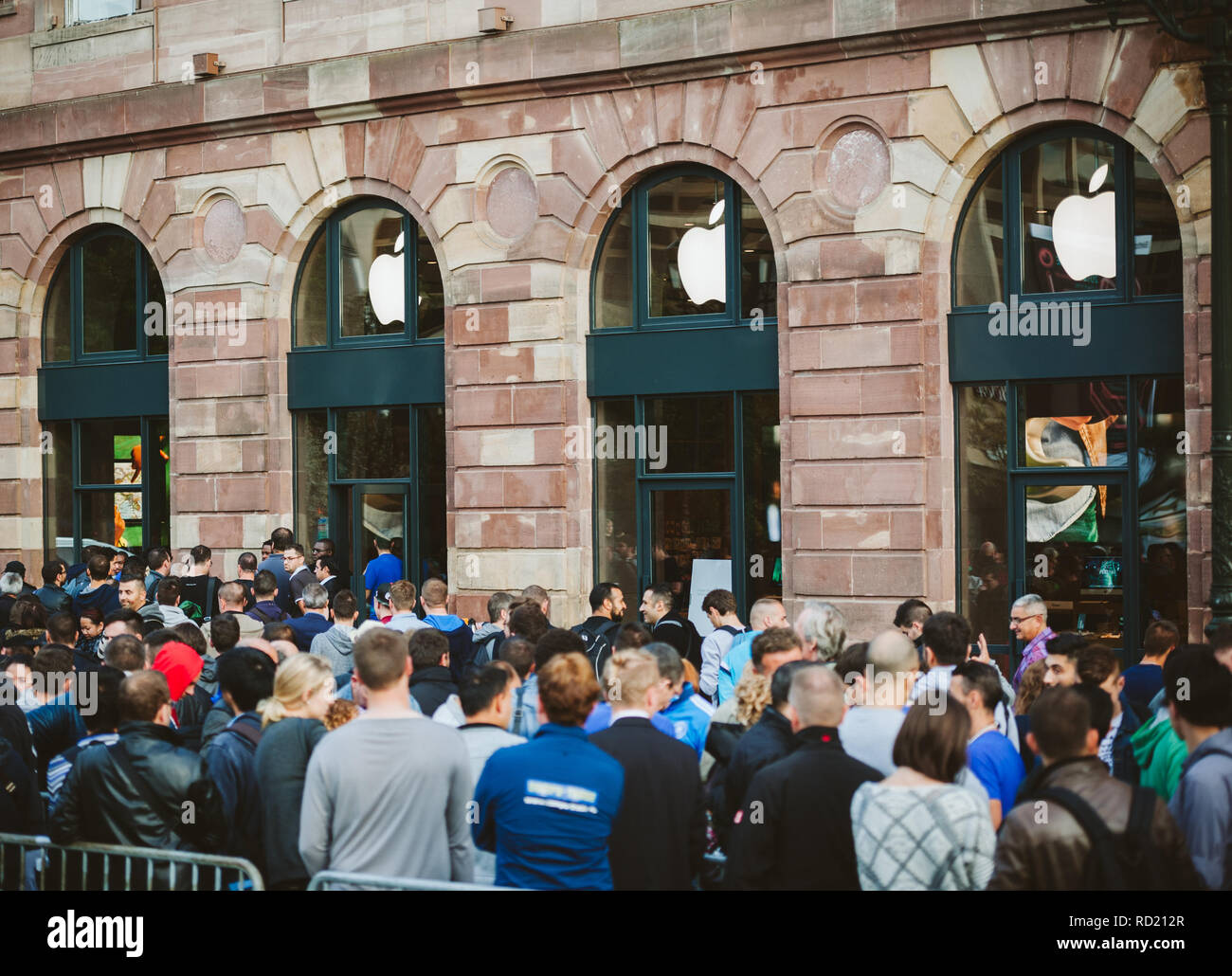 STRASBOURG, FRANCE - SEP, 19 2014: Adult and kids in line queue in front of Apple Store with customers waiting in line to buy the latest iPhone iPad Apple Watch and notebook Stock Photo