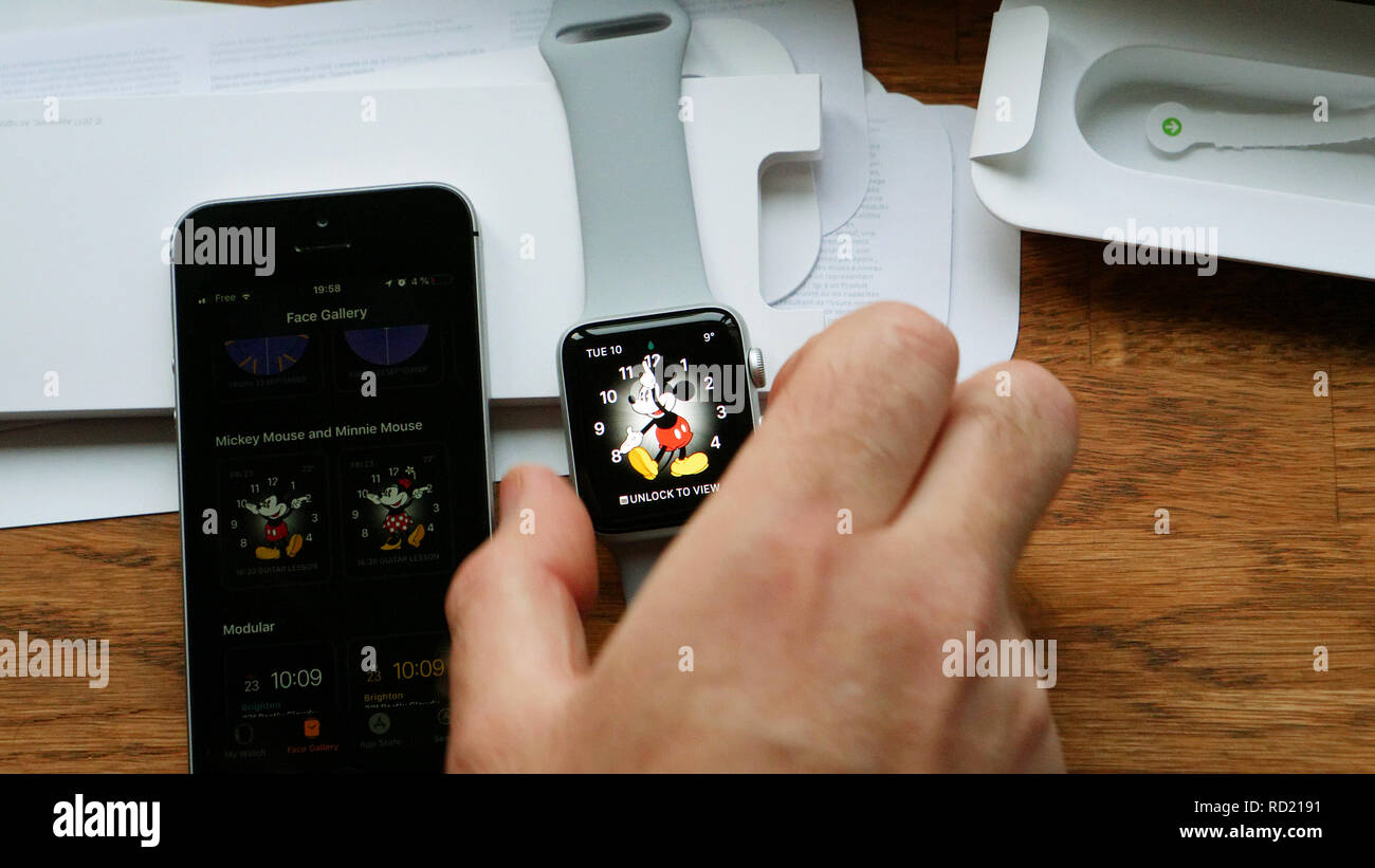 PARIS, FRANCE - APR 12 2018: POV man unboxing unpacking latest Apple Watch Series 3 GPS LTE smartwatch wearable computer Disney Mickey Mouse watch face setting - Stock Image