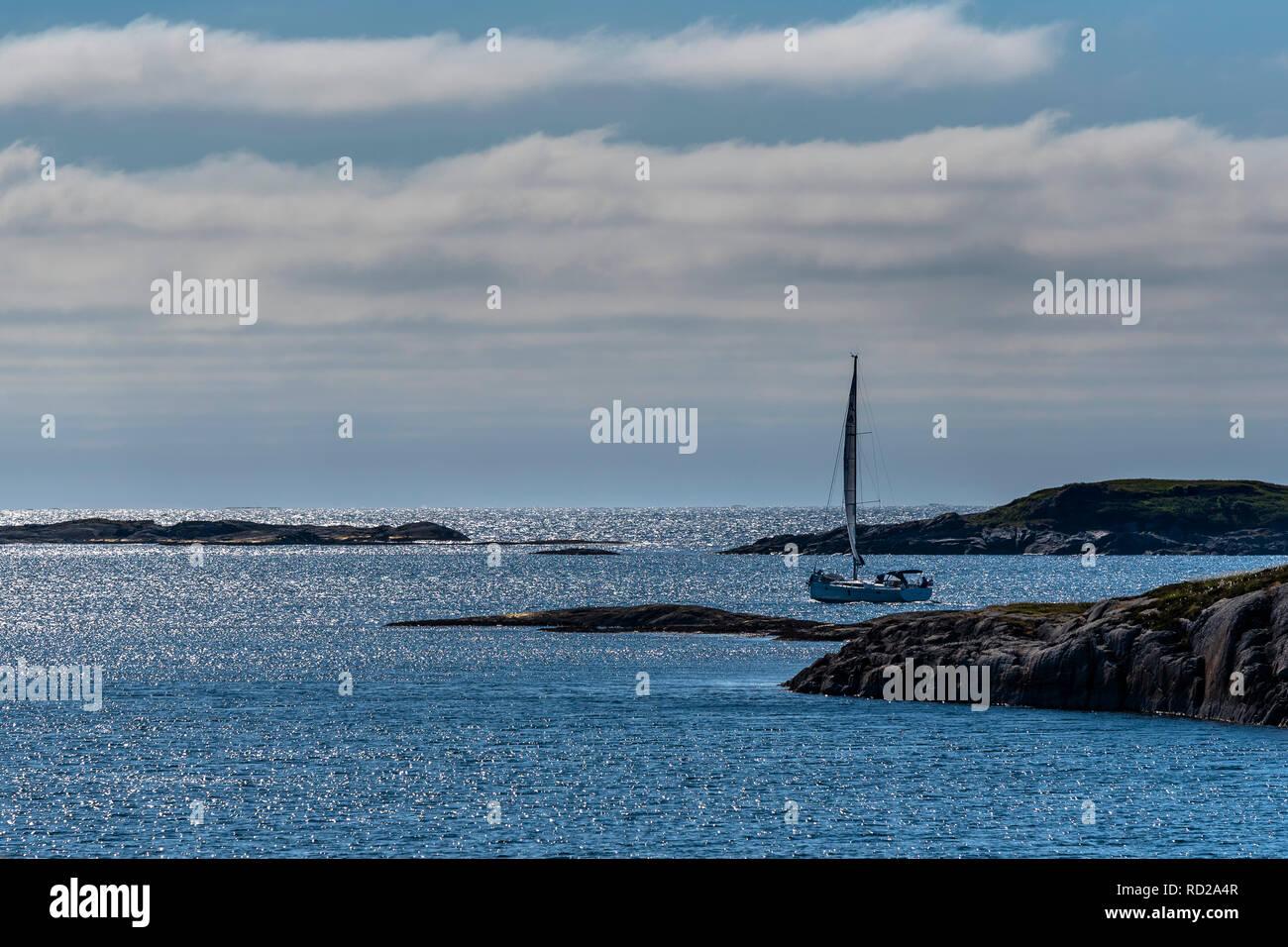 Samotna żaglówka na błyszczącym granatowym oceanie pomiędzy wysepkami pod zachmurzonym niebem. Norwegia, okolice Bud. - Stock Image