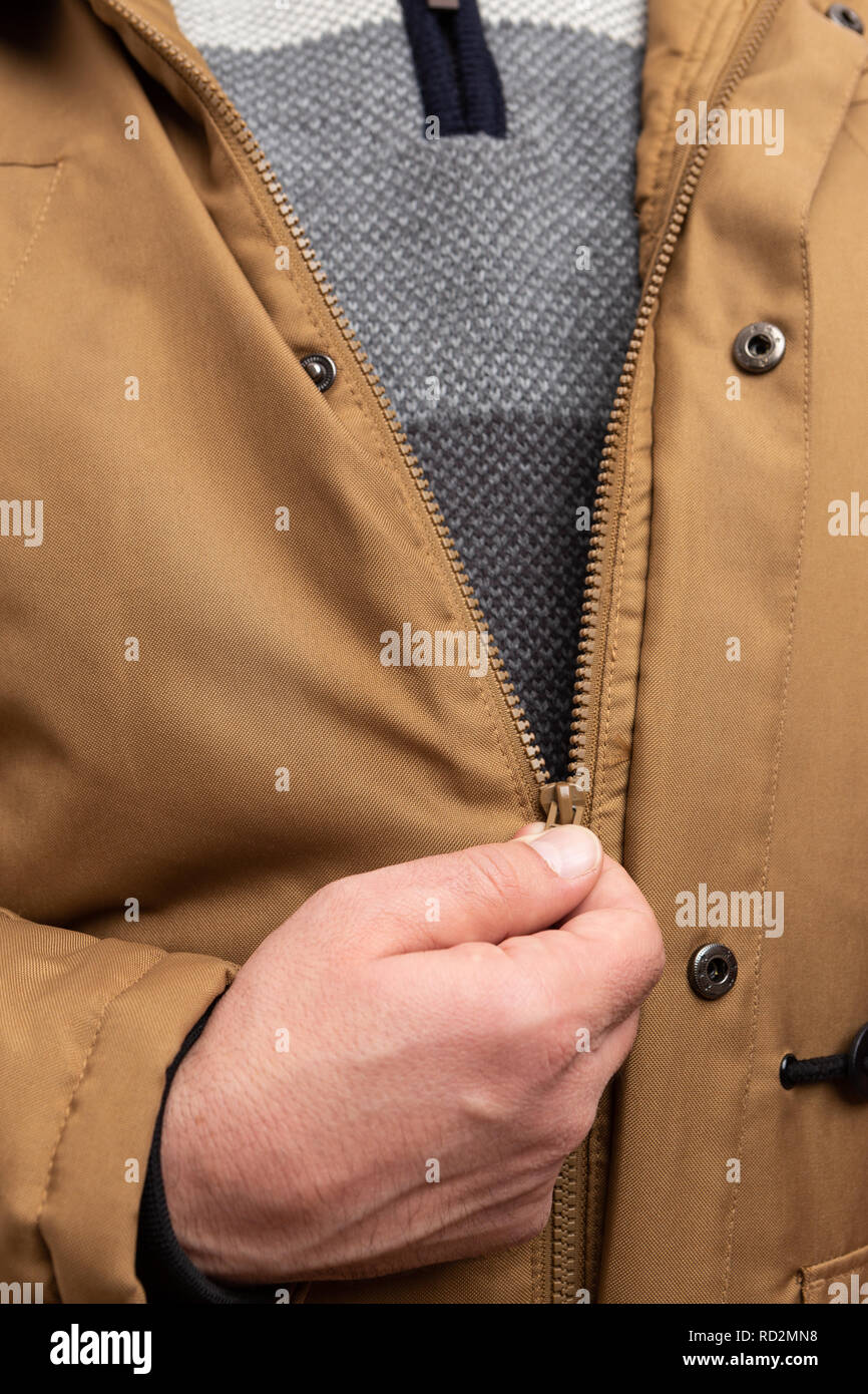 Close-up of man zipping winter jacket as cold weather fashion concept isolated on white studio background - Stock Image