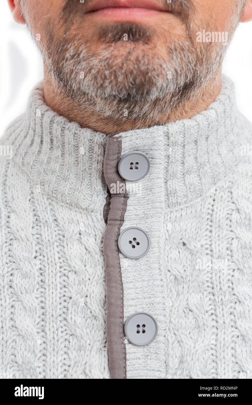 Close-up of buttoned-up grey jumper collar wore by man with beard as winter knitwear fashion concept isolated on white background - Stock Image