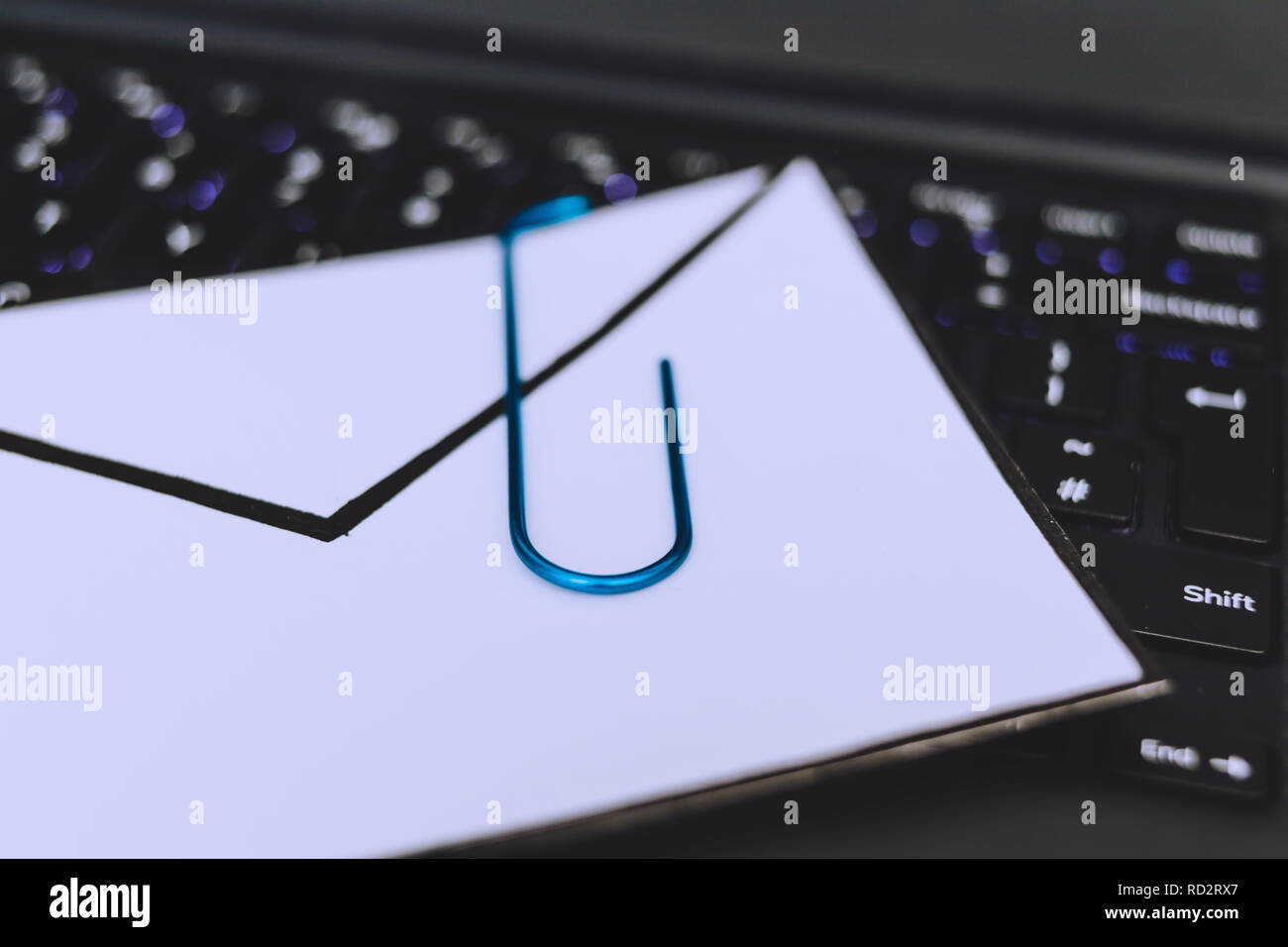 laptop keyboard with envelope and clip symbol of email attachments, close-up shot at shallow depth of field - Stock Image