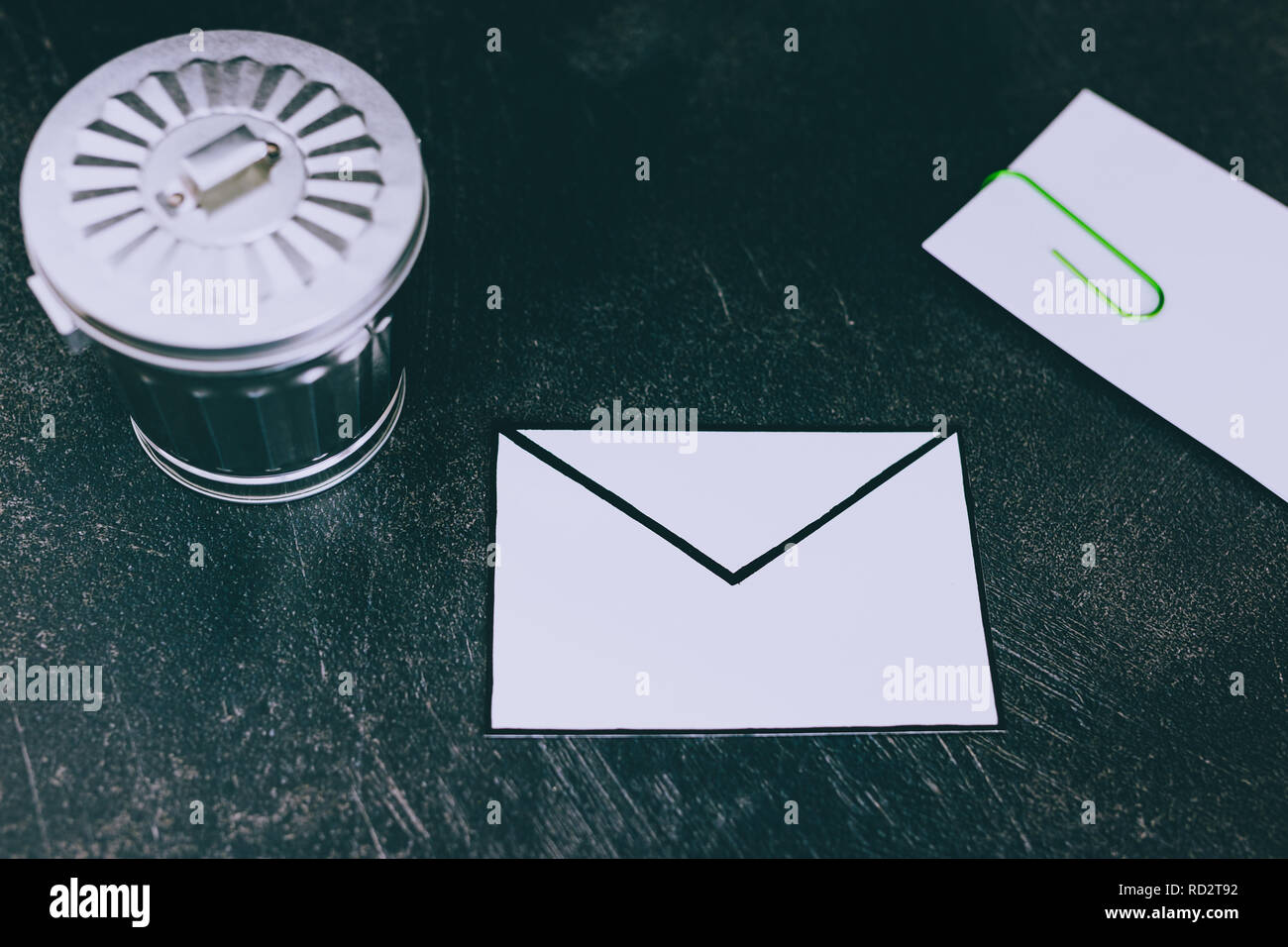 envelope with clip symbol of email and attachments with trash can next to it, concept of spam and unwanted emails - Stock Image