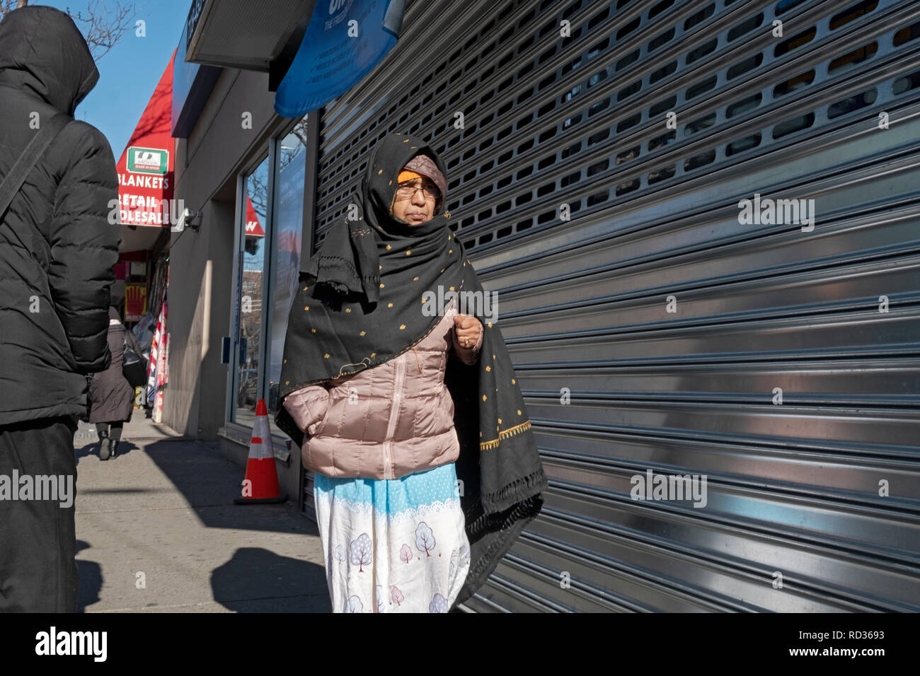 An older Muslim woman wearing a winter coat and niqab walking on 74th Street in Jackson Heights, Queens, New York City. - Stock Image