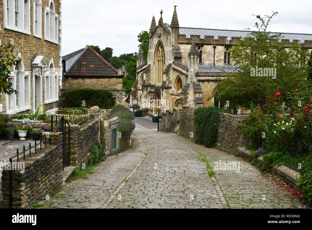 Gentle Street in Frome, Somerset descends to St Johns Church.This steep cobbled street used  as a set in many films. - Stock Image