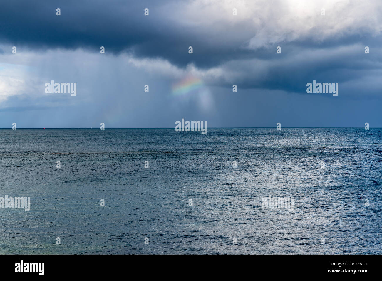 Rainclouds and a rainbow over the North Sea in Benthall, Northumberland, England, UK - Stock Image