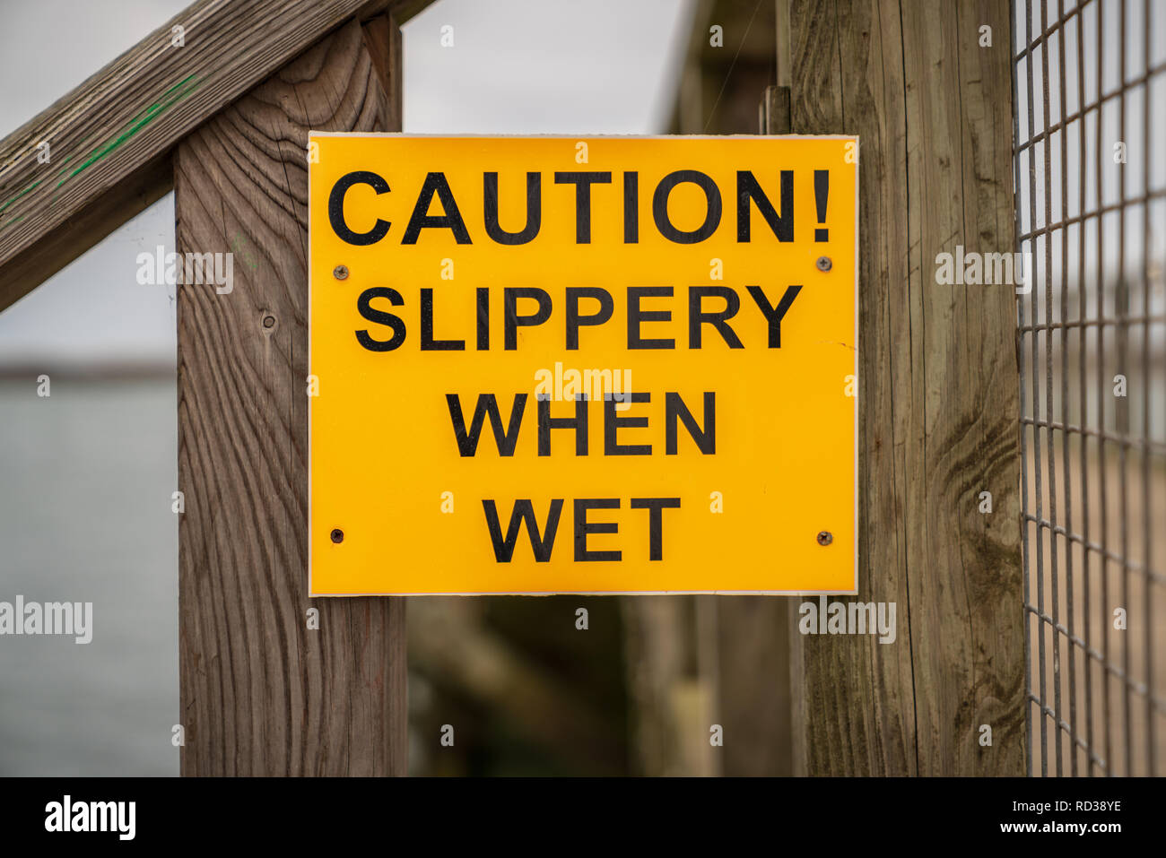 Sign: Caution! Slippery when wet, seen in Amble in Northumberland, England, UK - Stock Image