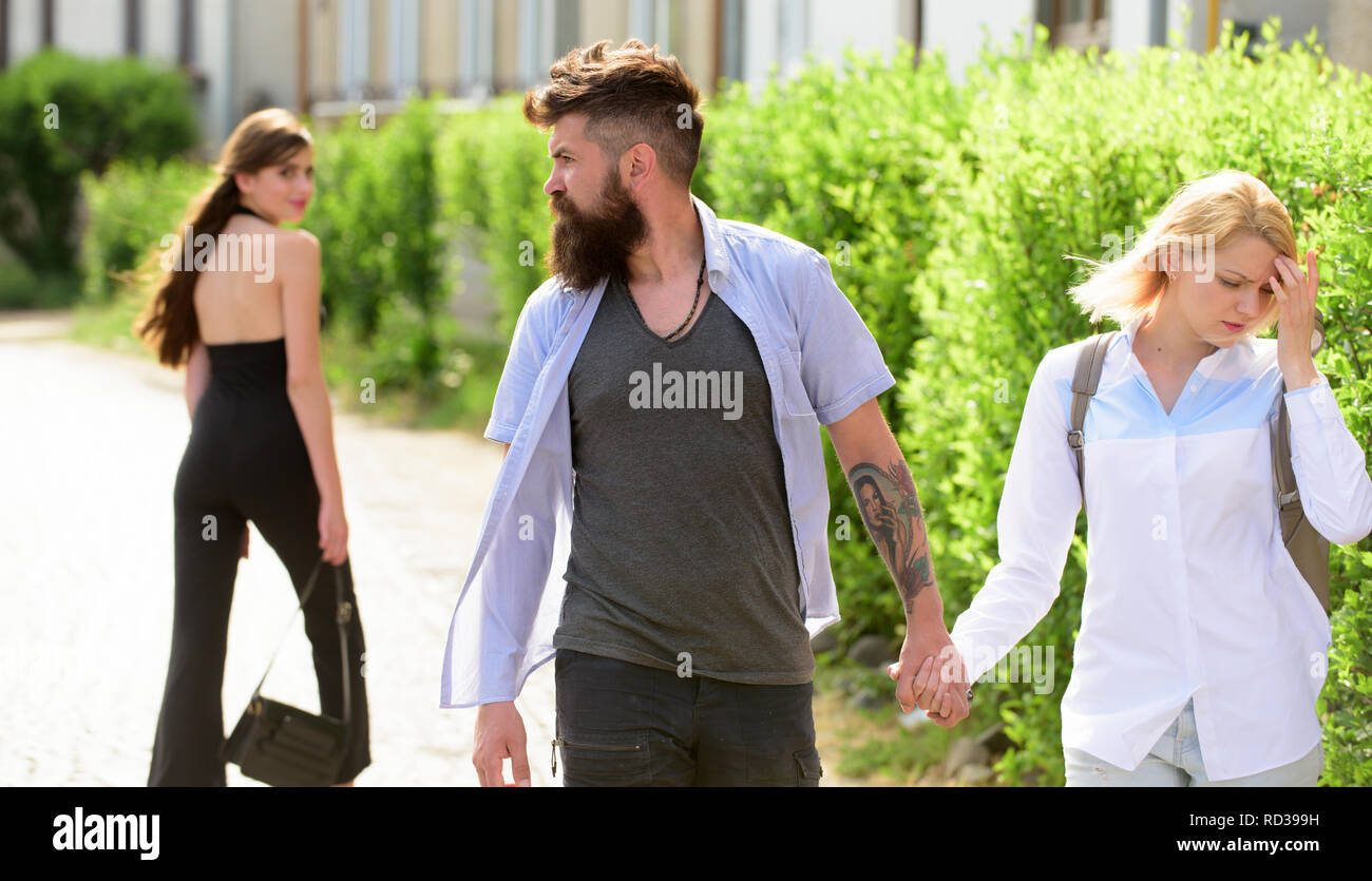 Womaniser. Unfaithful love. Love triangle and threesome. Man cheating his wife or girlfriend. Bearded man looking at other girl. Hipster choosing between two women. Betrayal and infidelity - Stock Image