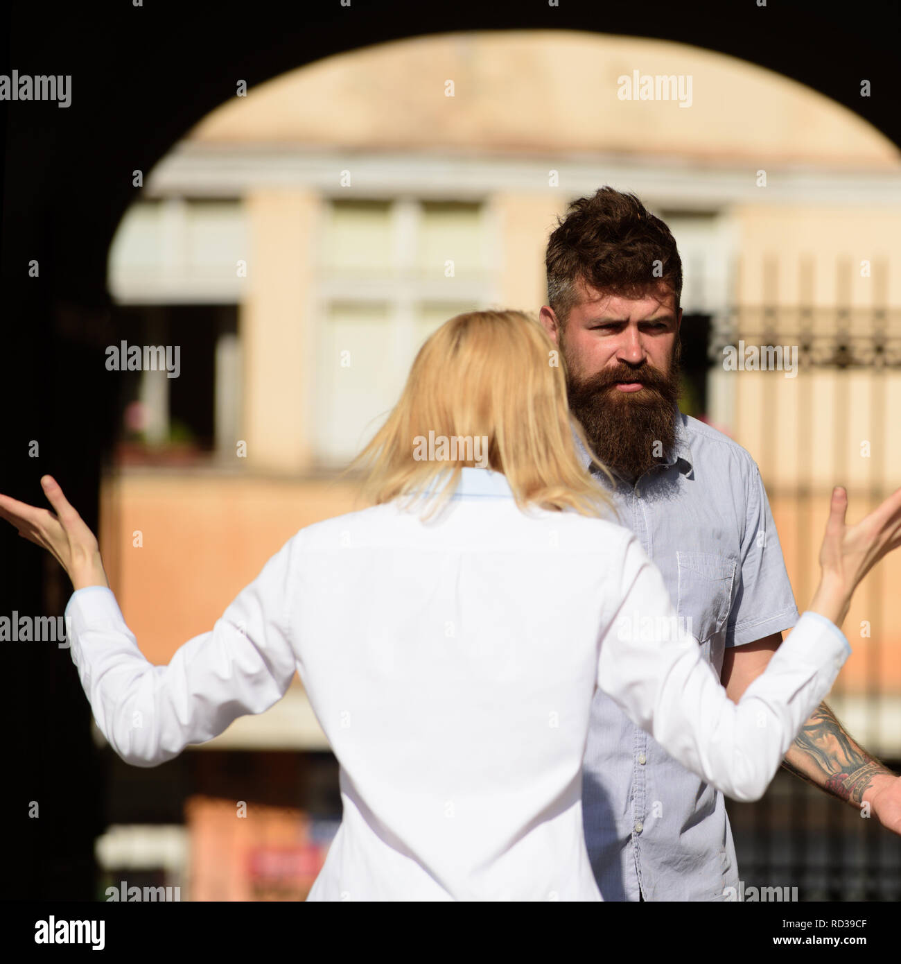 I dont understand you. Woman shouting and gesturing at bearded man. Couple in love quarreling on street. Conflict management in couple relationship. Conflict between lovers. Family conflict - Stock Image