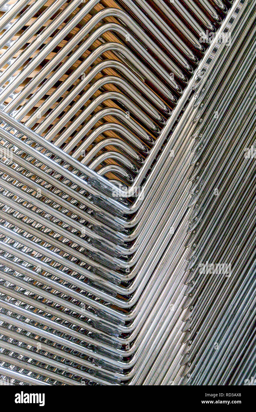 Abstract image of the metallic legs of stacked chairs - Stock Image