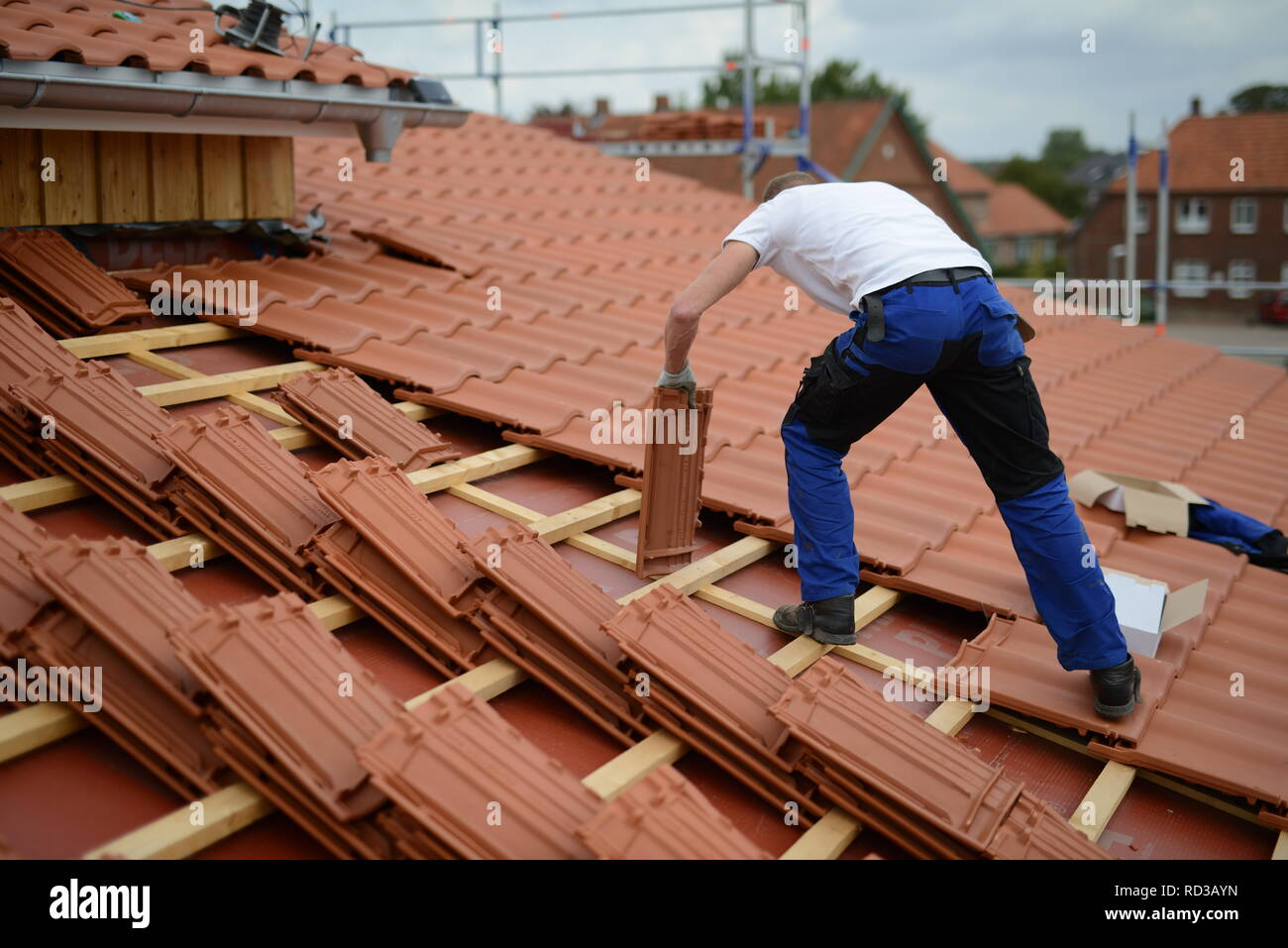 Dach Baustelle neu mit roten Dachziegeln. Dachdecker Bauarbeiter in weißem T-Shirt und Arbeitshandschuhen in Deutschland. Mann bei der Arbeit. - Stock Image