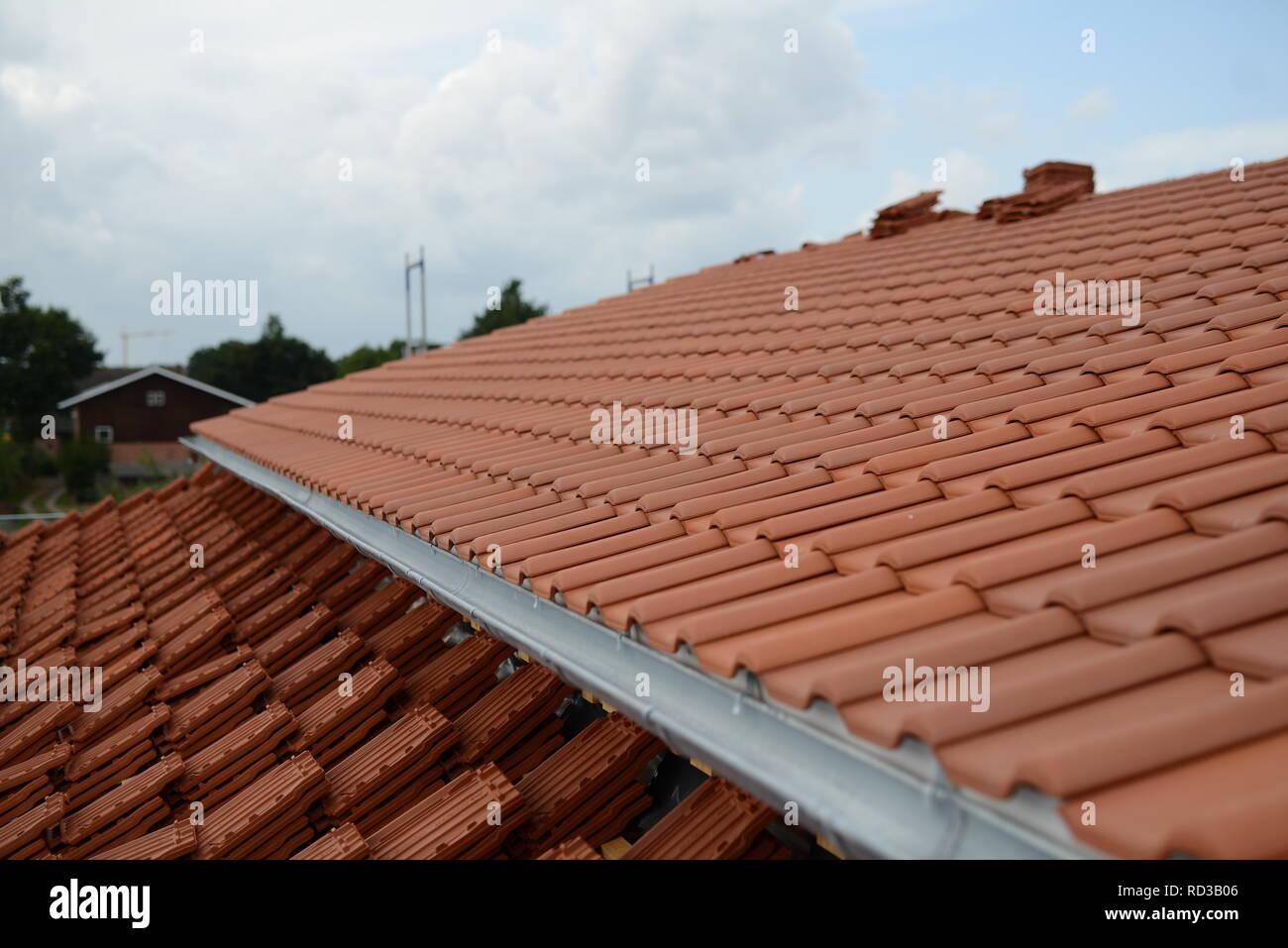 Freier Platz auf Dach Baustelle neu mit roten Dachziegeln Tonpfannen eindecken. Dachdecker Arbeit Handwerk Deutschland. Haus Dach Dachpfannen neu - Stock Image