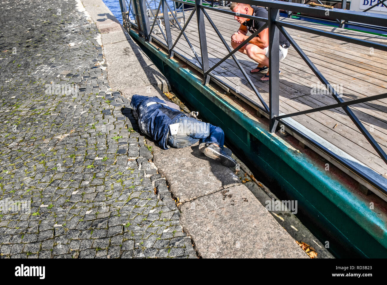 St. Petersburg, Russia - September 11 2018: A homeless man sleeps as another man tries to wake him on a sidewalk near a boat dock on the Neva River. - Stock Image