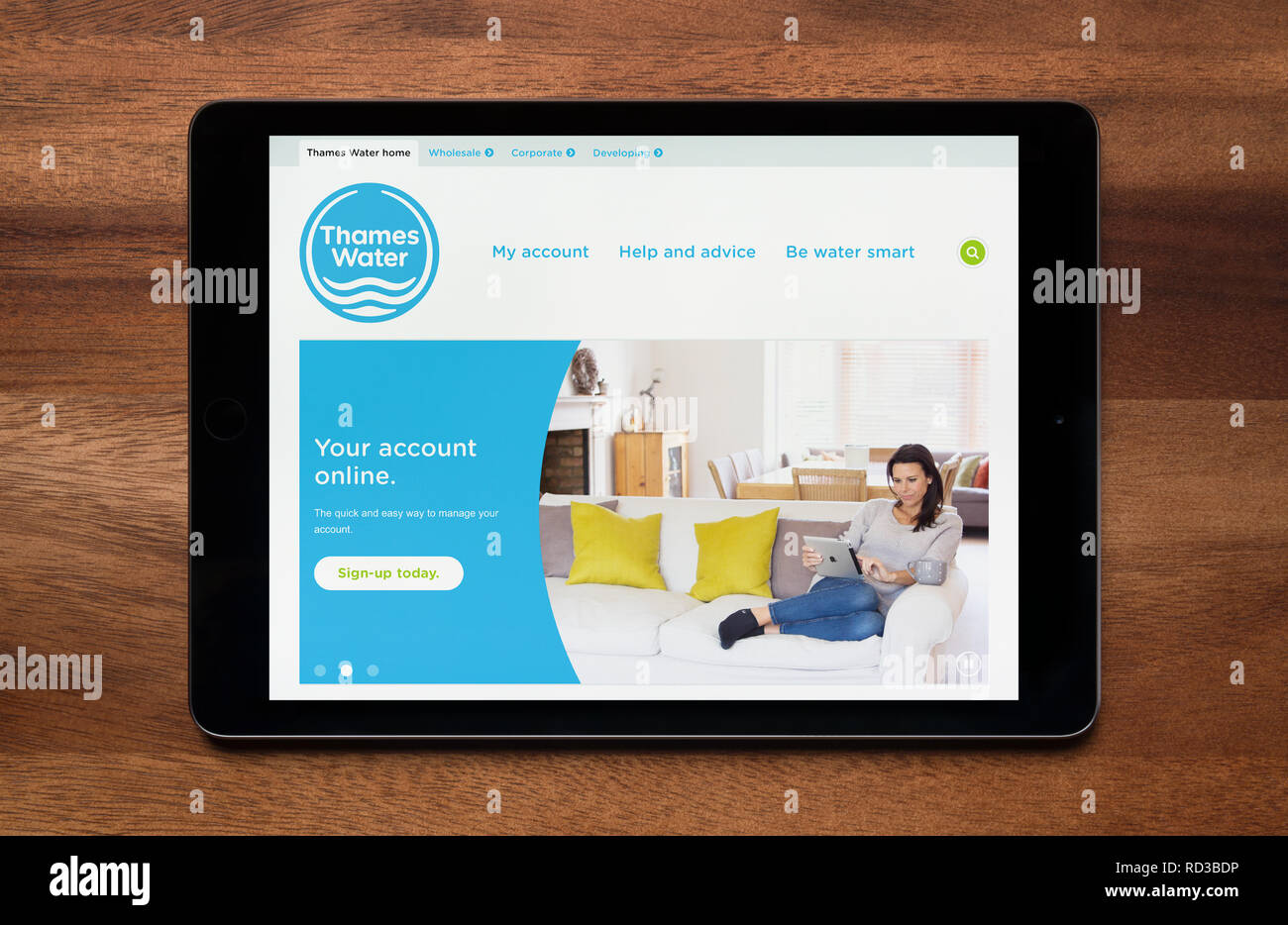 The website of Thames Water is seen on an iPad tablet, which is resting on a wooden table (Editorial use only). - Stock Image