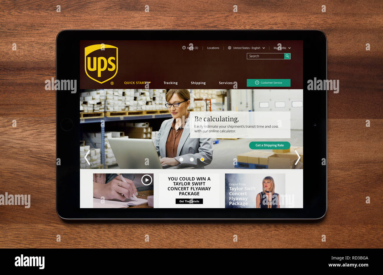 The website of UPS is seen on an iPad tablet, which is resting on a wooden table (Editorial use only). - Stock Image