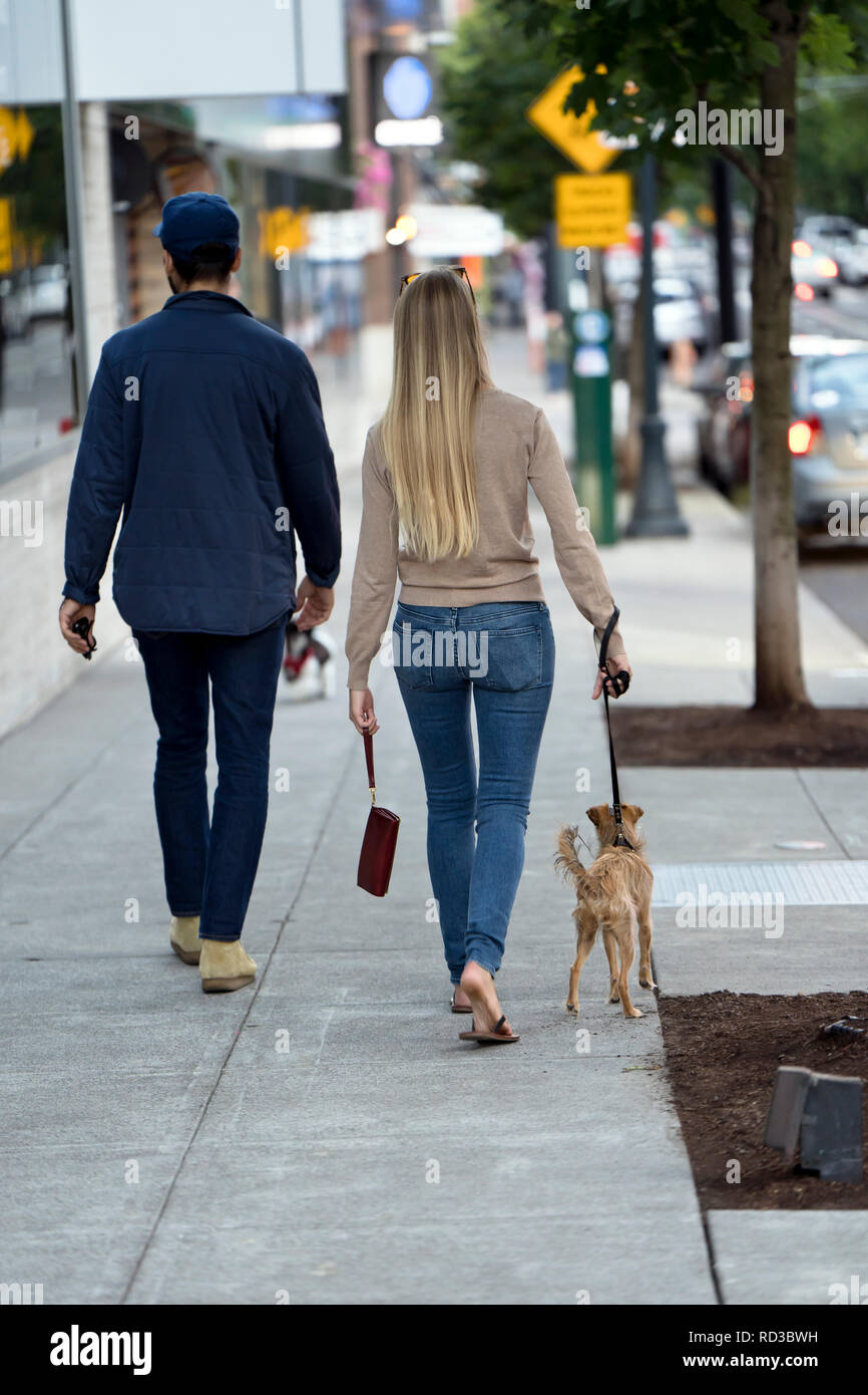 Young beautiful fashionable couple a man and a woman in great shape are walking with a dog along the street of a modern city, enjoying the city landsc Stock Photo