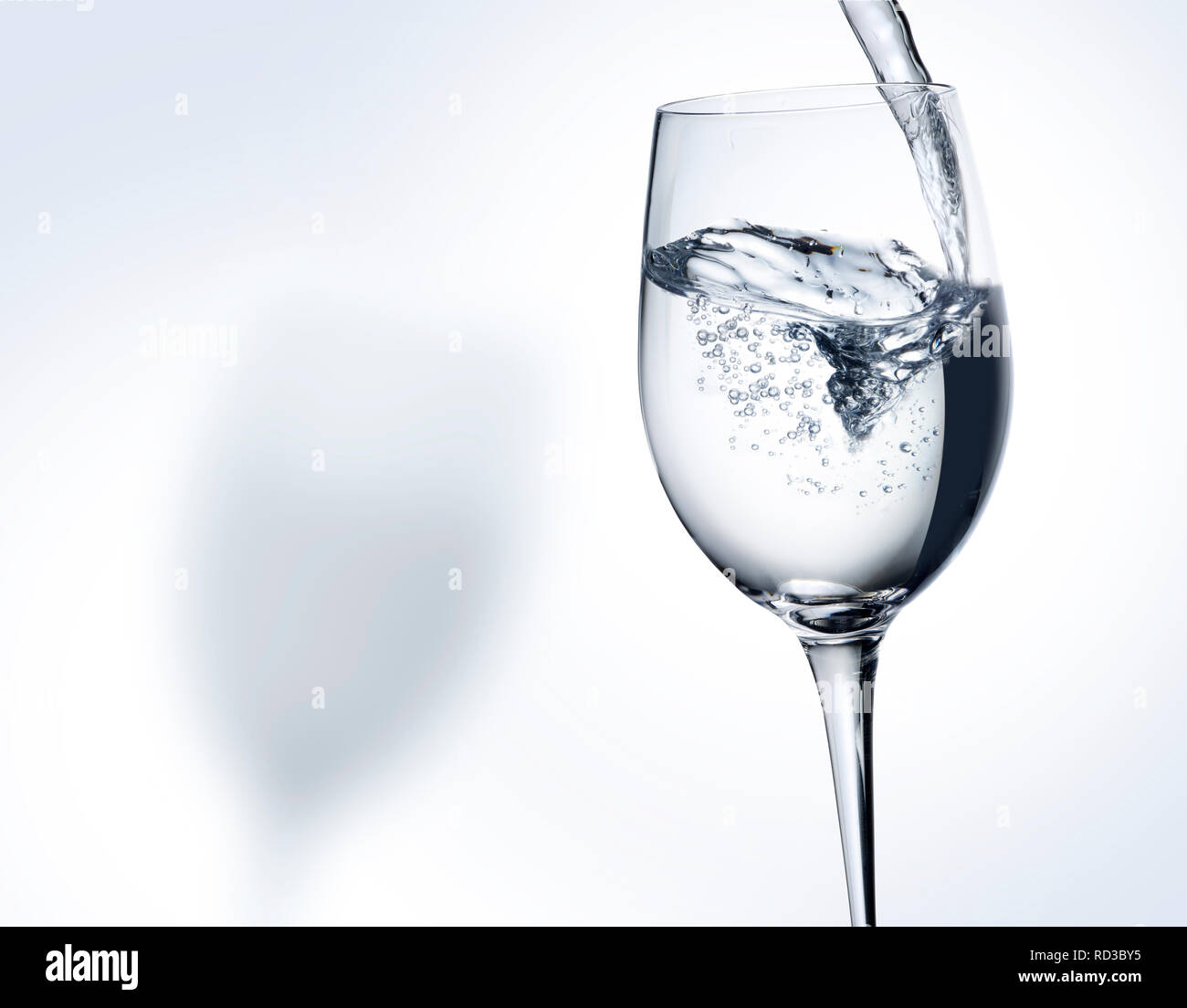 Monochrome image of water pouring into a wine glass, space for copy - Stock Image