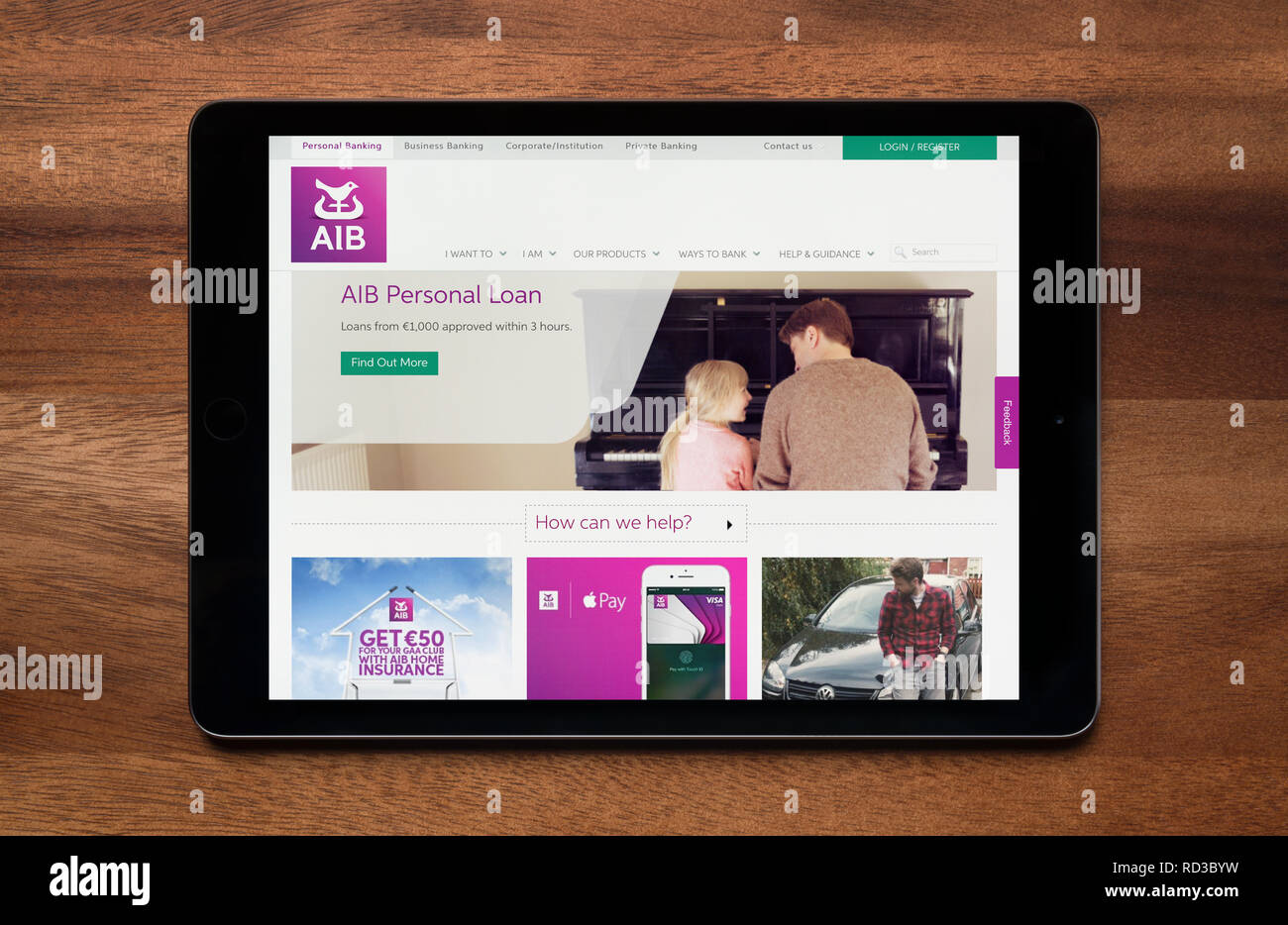 The website of AIB (Allied Irish Banks) is seen on an iPad tablet, which is resting on a wooden table (Editorial use only). - Stock Image