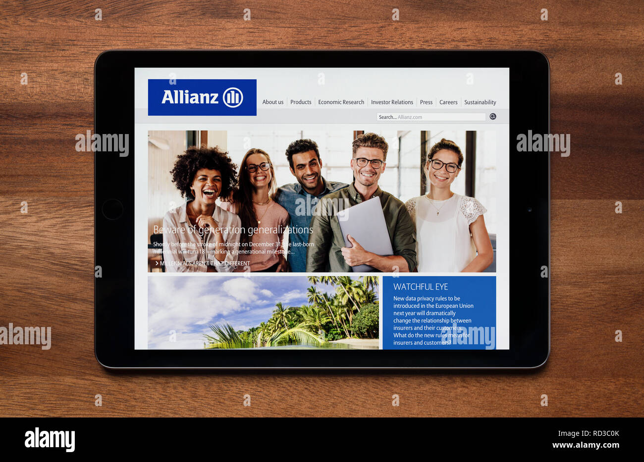 The website of Allianz insurance is seen on an iPad tablet, which is resting on a wooden table (Editorial use only). - Stock Image
