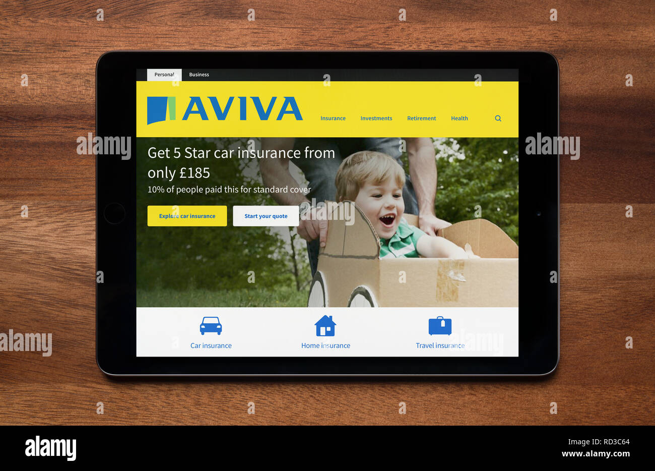 The website of Aviva insurance is seen on an iPad tablet, which is resting on a wooden table (Editorial use only). - Stock Image