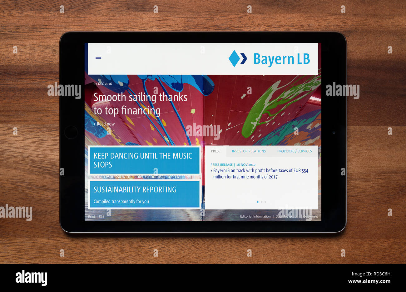 The website of Bayern LB is seen on an iPad tablet, which is resting on a wooden table (Editorial use only). - Stock Image