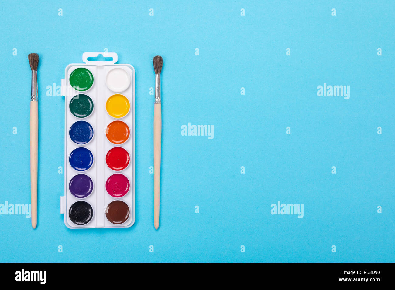 Watercolor paints and brushes in white box, isolated on blue background Stock Photo