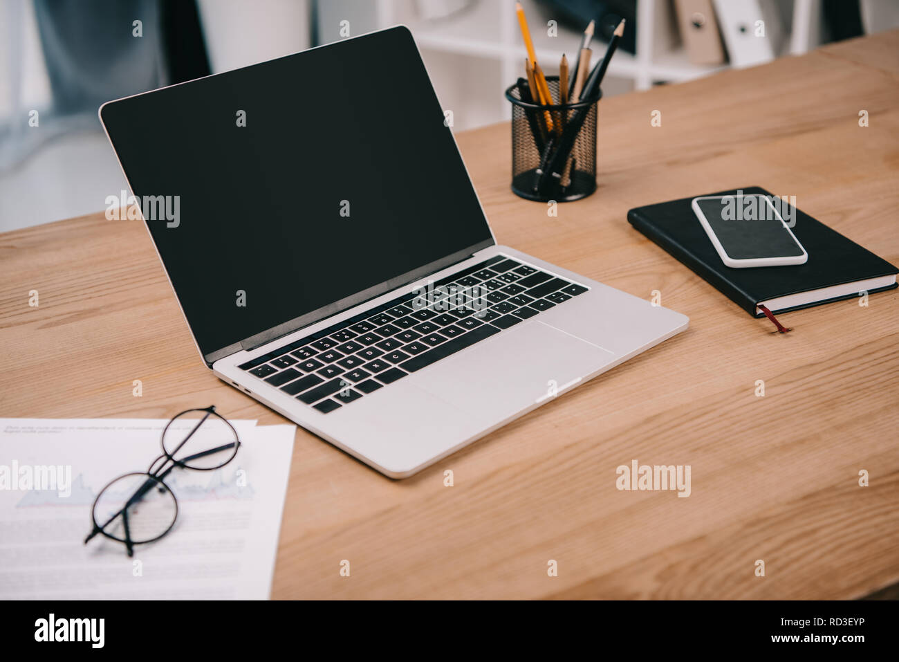 laptop with blank screen, business documents, smartphone and office supplies at workplace - Stock Image