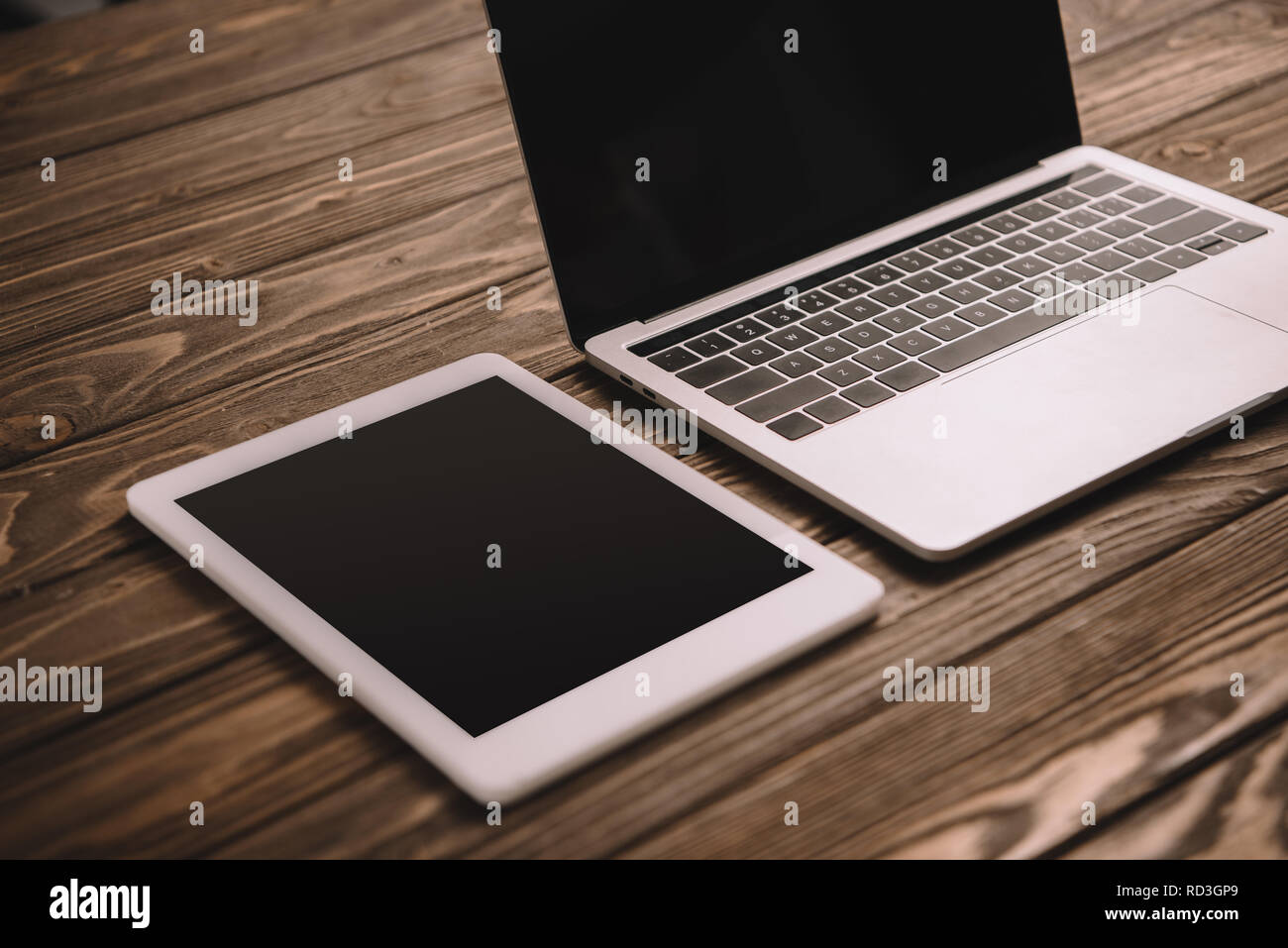 digital tablet and laptop with blank screens on wooden table - Stock Image