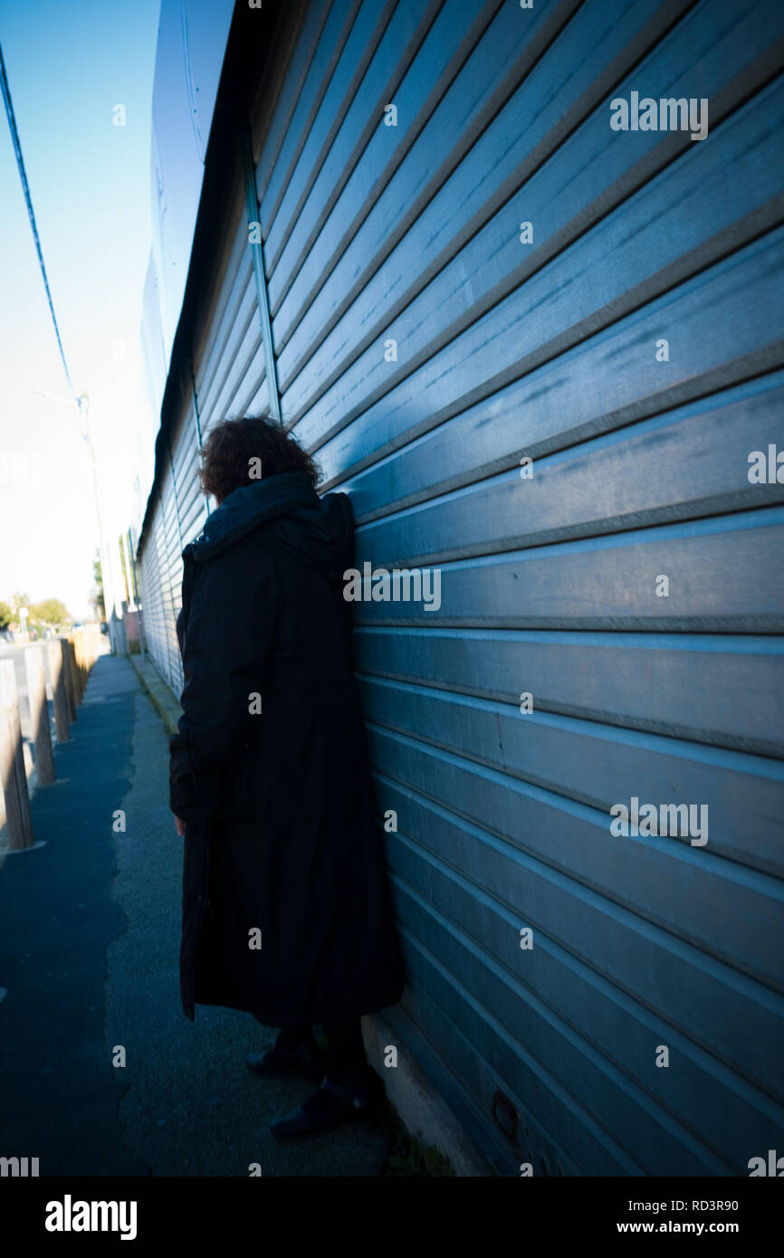 an elderly woman leans against metal shutters in a shopping precinct on a cold autumn day - Stock Image
