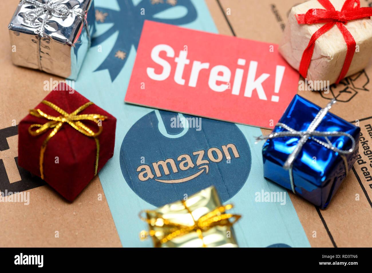 Strike sign and presents on Amazon package, Streik-Schild und Geschenke auf Amazon-Paket - Stock Image
