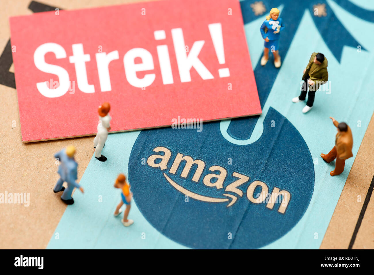 Strike sign and miniature figures on Amazon package, Streik-Schild und Miniaturfiguren auf Amazon-Paket - Stock Image