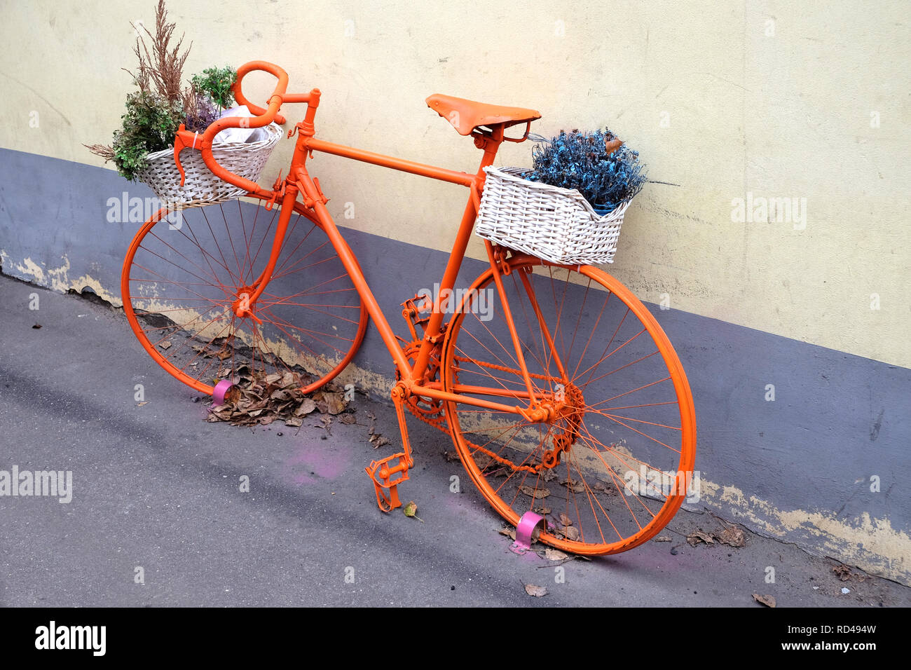 Retro style sport bike color orange with flower baskets as decoration outdoor near the wall side view - Stock Image
