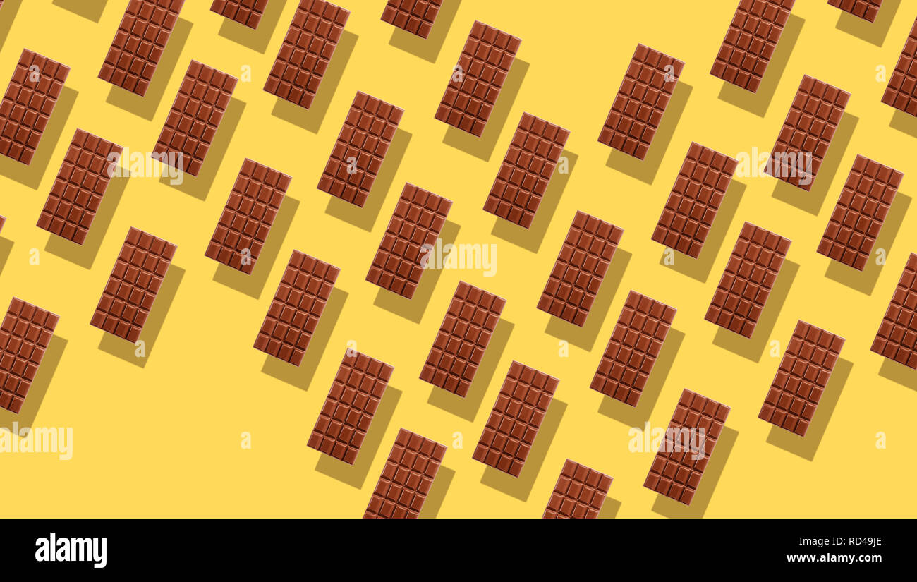 Pattern of small duplicating milk chocolate tablets on yellow background with shadows, viewed from above in full frame - Stock Image