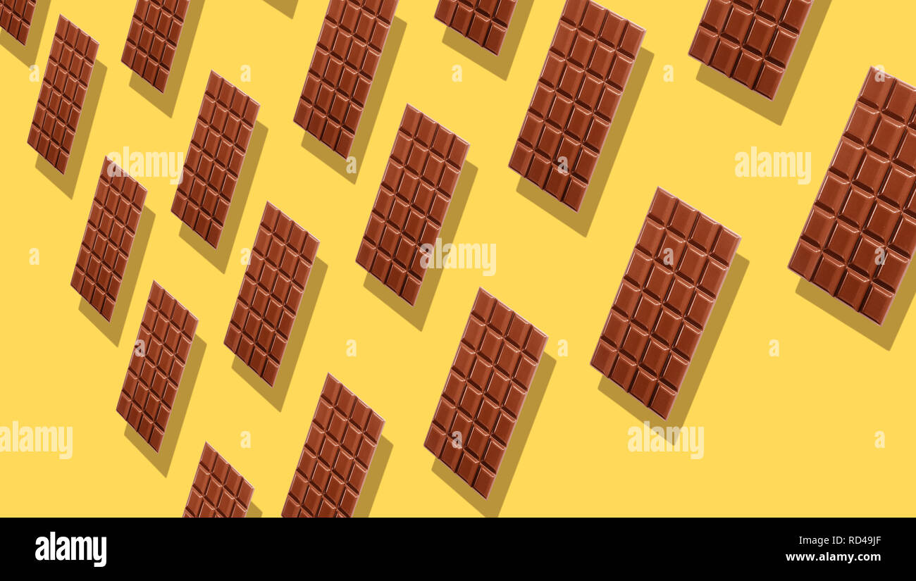 Milk chocolate tablets duplicating on yellow background with shadows viewed in perspective, and full frame. - Stock Image