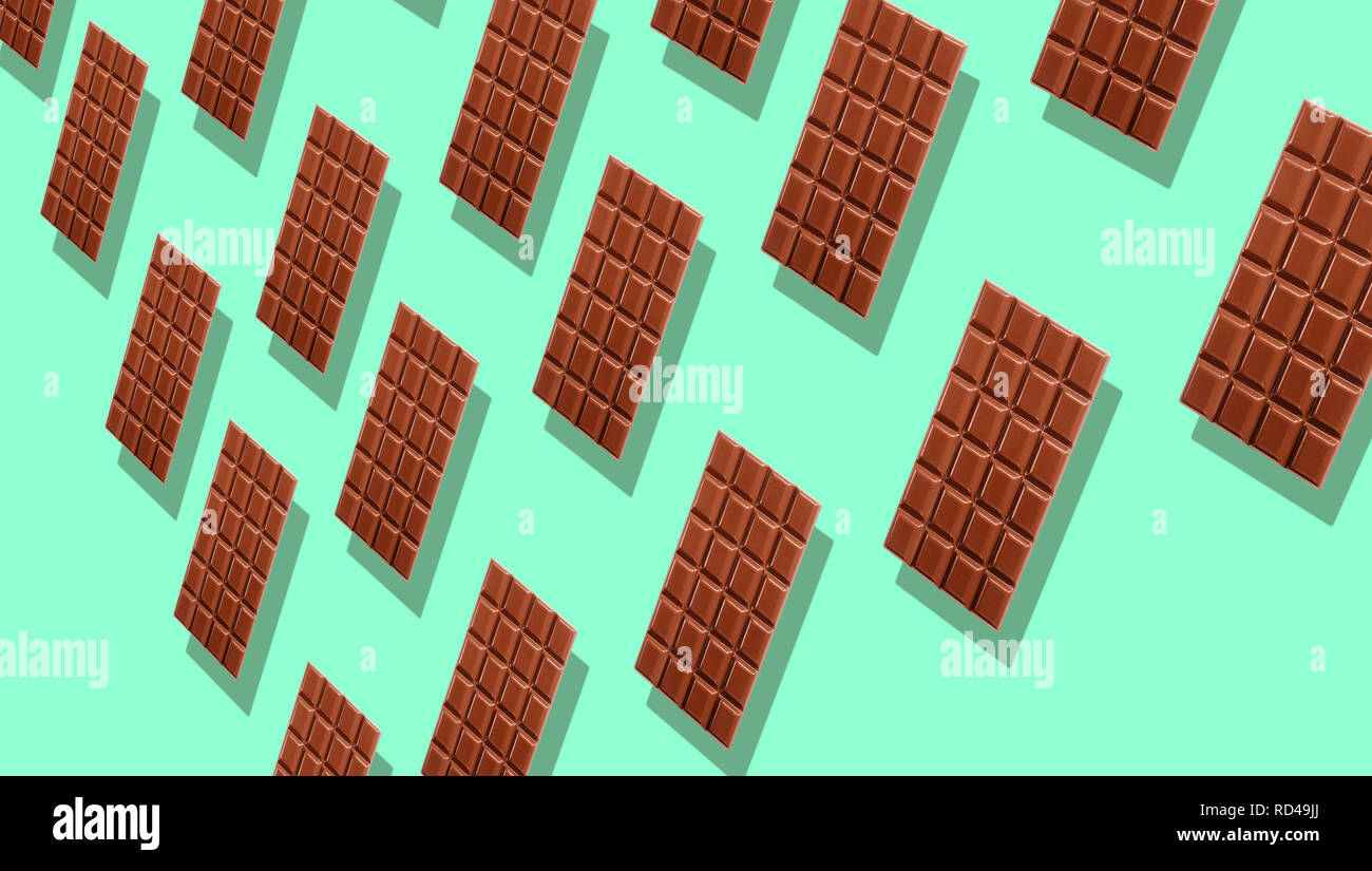 Pattern of many whole milk chocolate tablets with shadows on cyan background, viewed in perspective and full frame - Stock Image