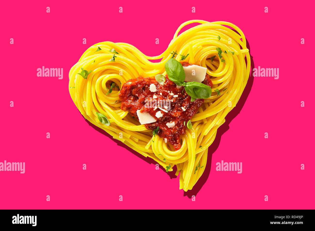 Decorative heart-shaped Italian pasta portion, formed of cooked spaghetti, topped with tomatoes, basil, and parmesan cheese, viewed in close-up, from  - Stock Image